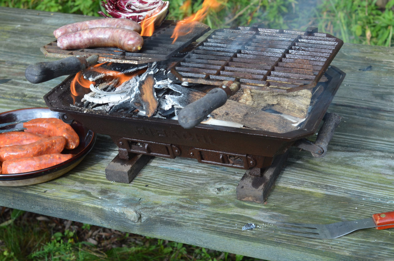 Hibachi Tabletop Grill On Picnic Table Flames Brats Radicchio Italian Sausages Cooking