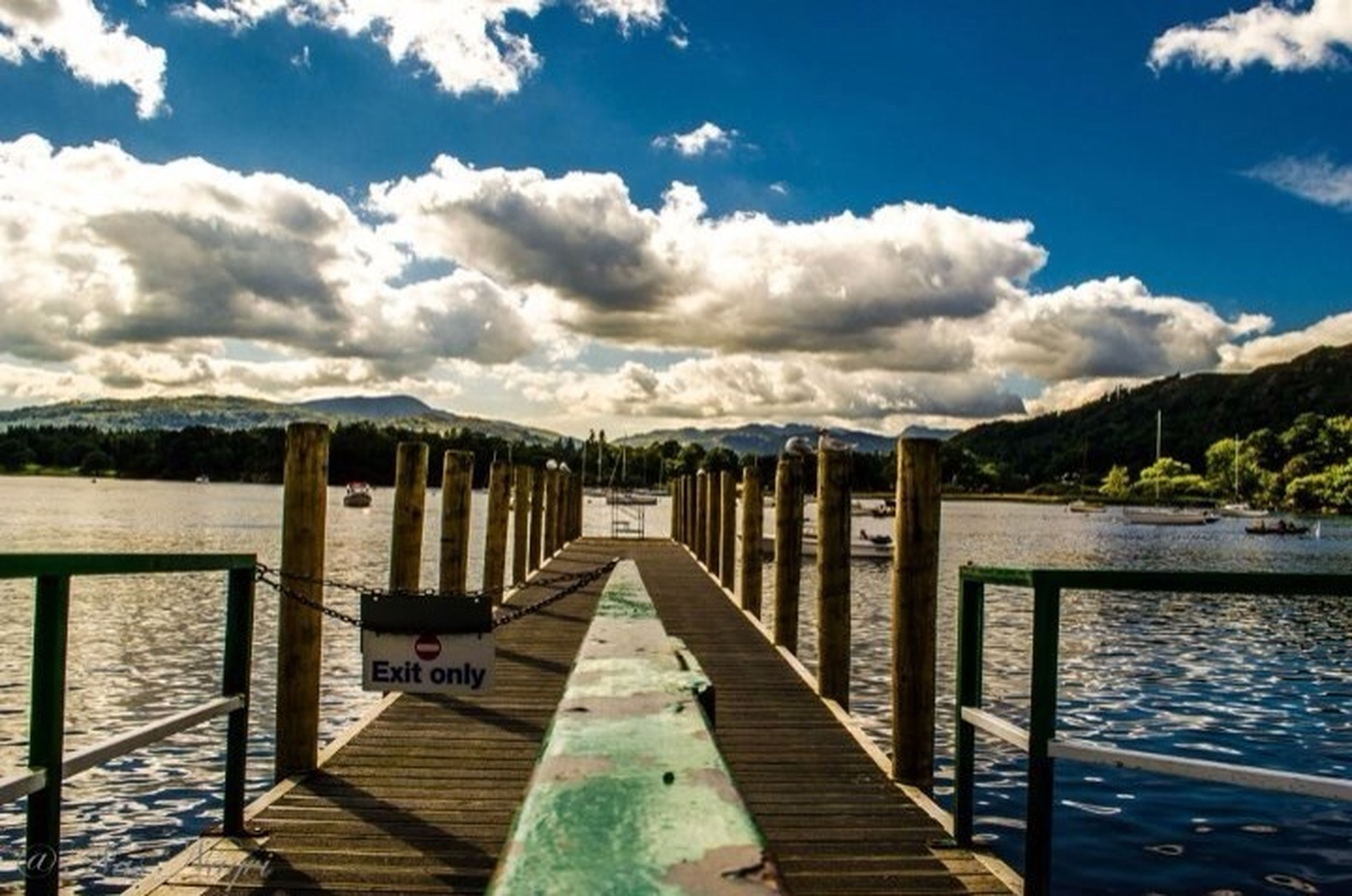 water, sky, pier, the way forward, jetty, lake, tranquil scene, railing, mountain, tranquility, cloud - sky, wood - material, scenics, cloud, nature, beauty in nature, blue, boardwalk, wood, sea