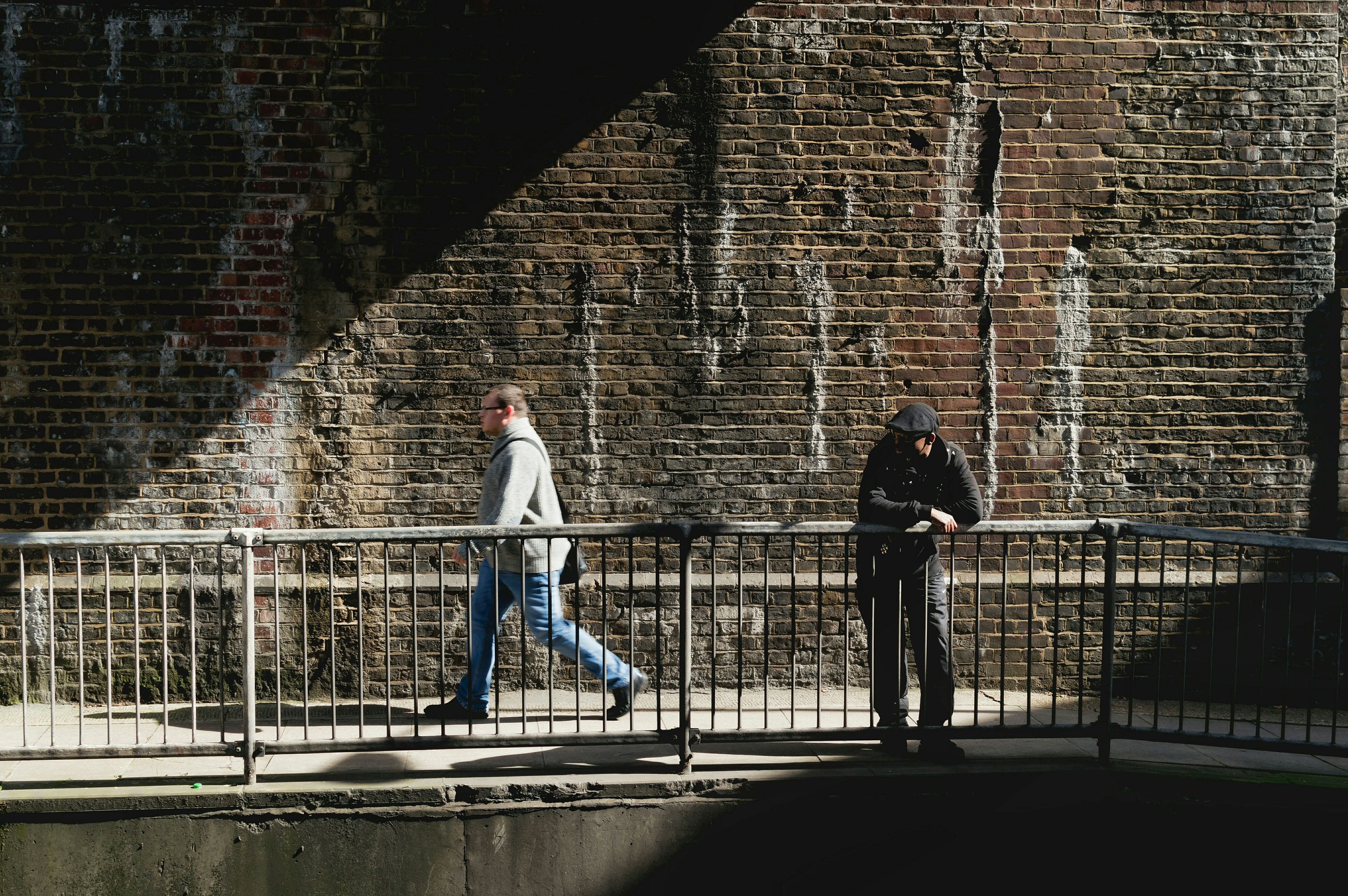 architecture, building exterior, built structure, lifestyles, full length, men, brick wall, leisure activity, bicycle, wall - building feature, railing, walking, building, person, city, side view, standing, casual clothing