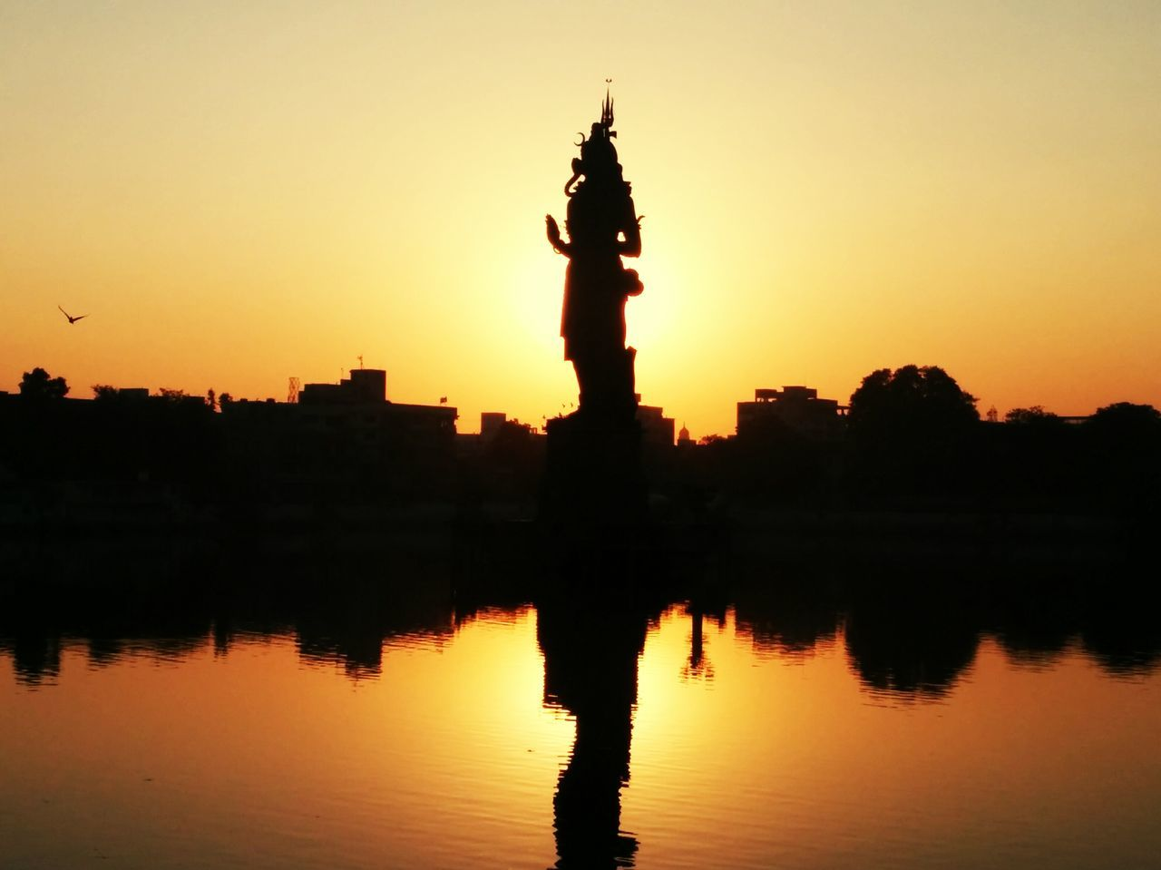 sunset, silhouette, reflection, orange color, architecture, statue, travel destinations, water, built structure, sky, travel, building exterior, beauty in nature, outdoors, lake, sculpture, no people, nature, scenics, gold colored, city, tree