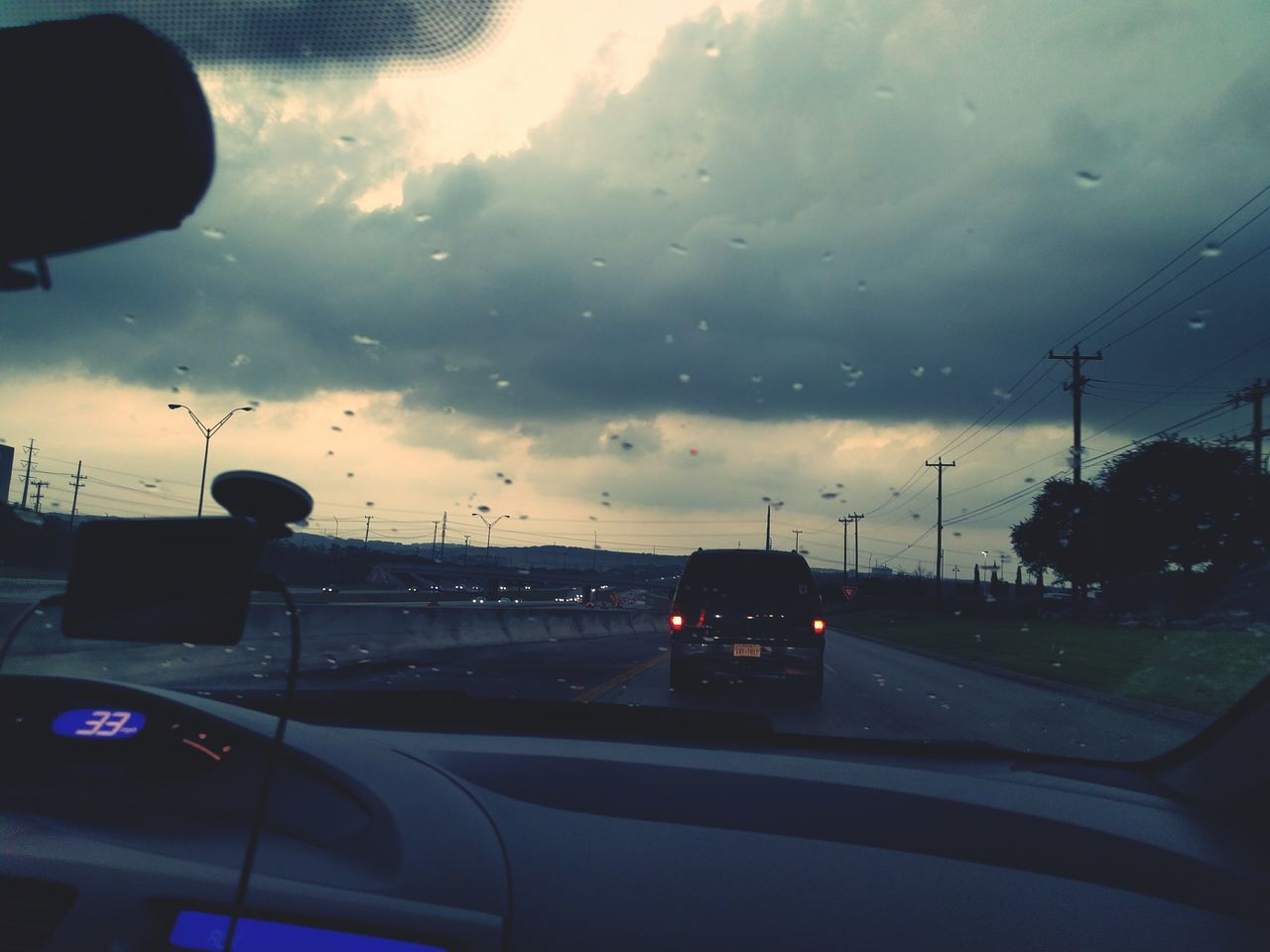 car, glass - material, transparent, transportation, land vehicle, car interior, windshield, vehicle interior, mode of transport, cloud - sky, road, sky, car point of view, sunset, drop, window, no people, side-view mirror, wet, road trip, nature, storm cloud, road sign, day, outdoors