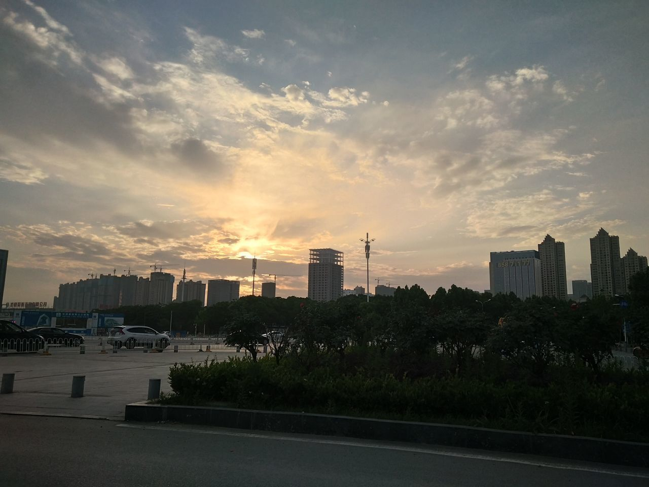 architecture, building exterior, city, sky, sunset, built structure, cloud - sky, skyscraper, modern, cityscape, growth, urban skyline, travel destinations, no people, city life, outdoors, tree, nature, day