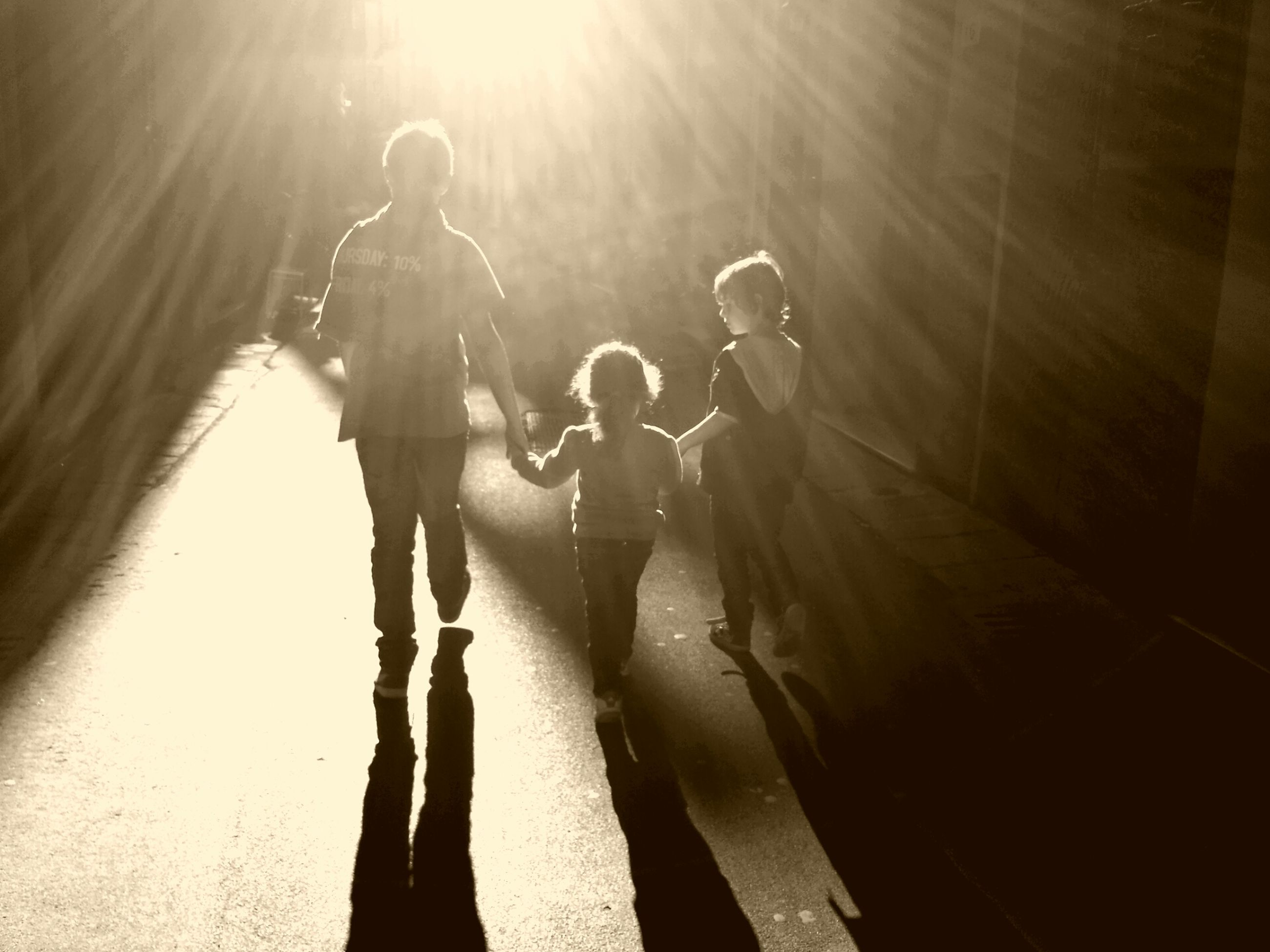 lifestyles, leisure activity, sunlight, standing, men, full length, shadow, person, silhouette, indoors, casual clothing, togetherness, three quarter length, walking, sunbeam, rear view, wall - building feature