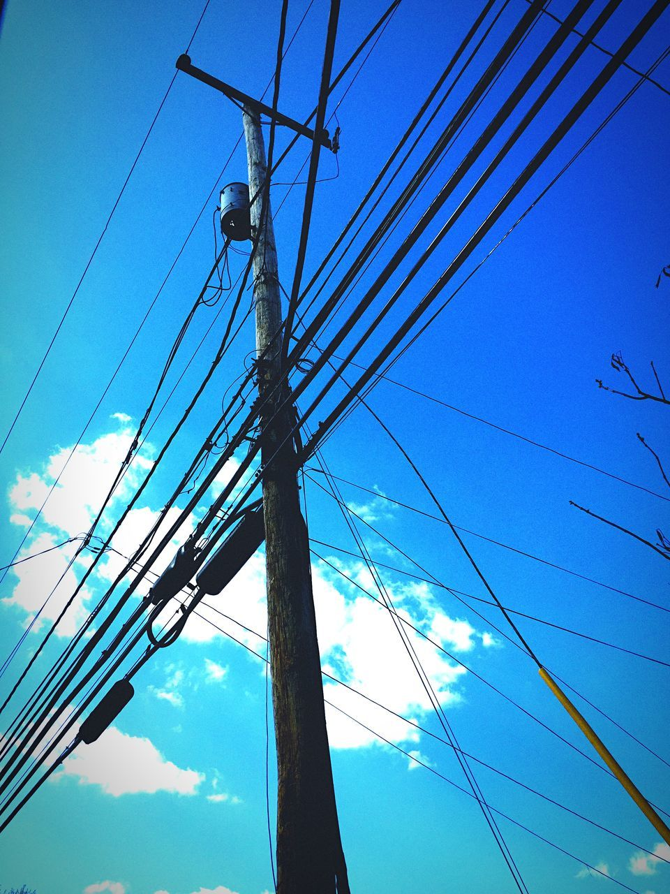 Low Angle View Of Telephone Pole Against Blue Sky