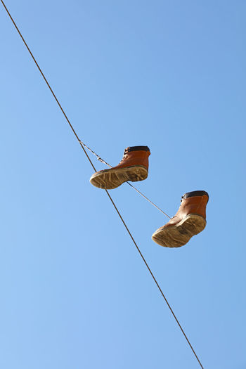 Suspended brown man shoes ower blue sky, low angle view Blue Cable Clear Sky Copy Space Dangle Day Foot Wear  Footwear High Low Angle View Military Military Style Overshoes Shoes Sky Streetart Streetphotography Suspended Swing Zippers