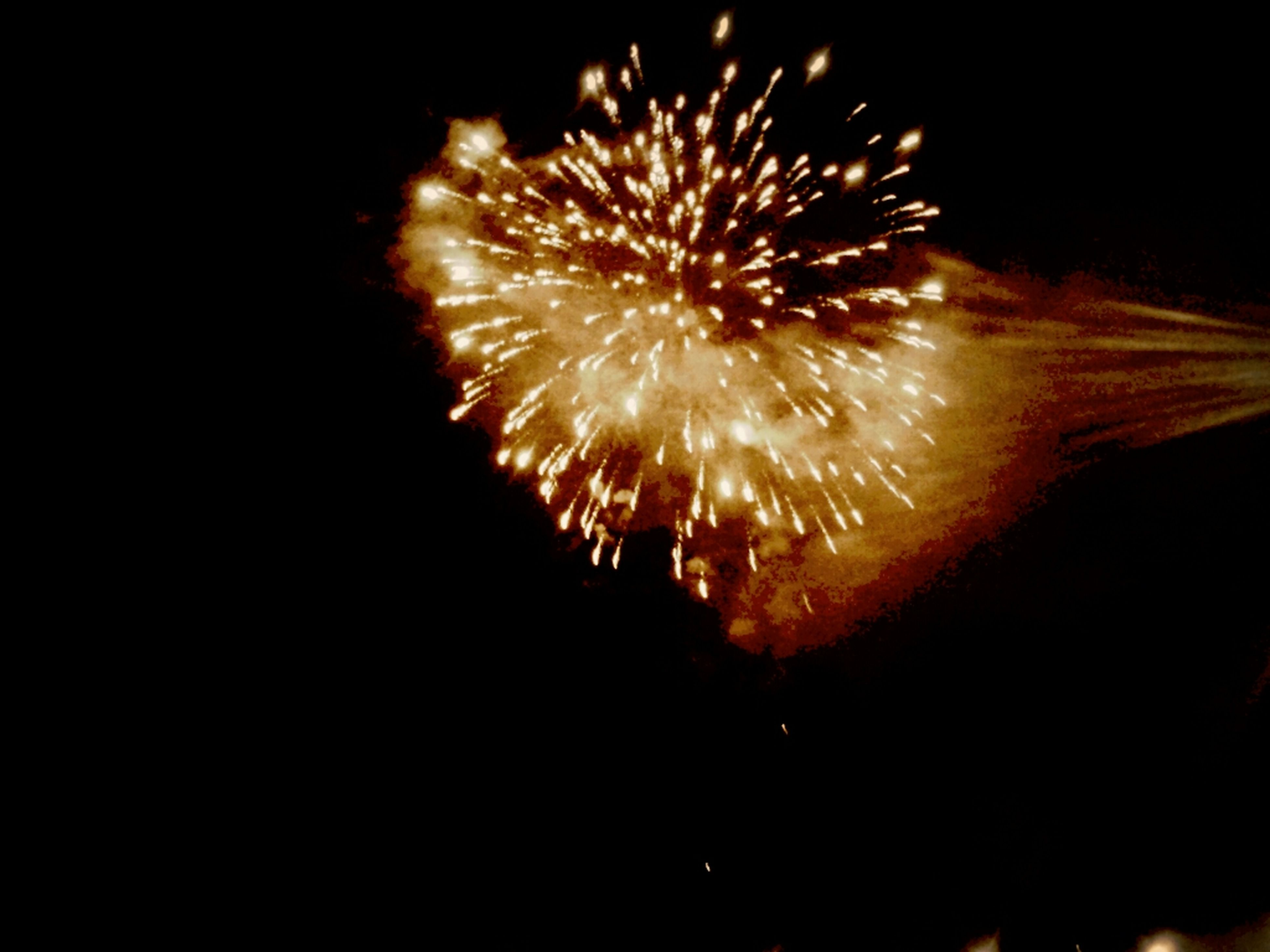 night, firework display, exploding, long exposure, illuminated, celebration, glowing, firework - man made object, motion, event, arts culture and entertainment, low angle view, sparks, firework, blurred motion, sky, entertainment, fire - natural phenomenon, celebration event, dark