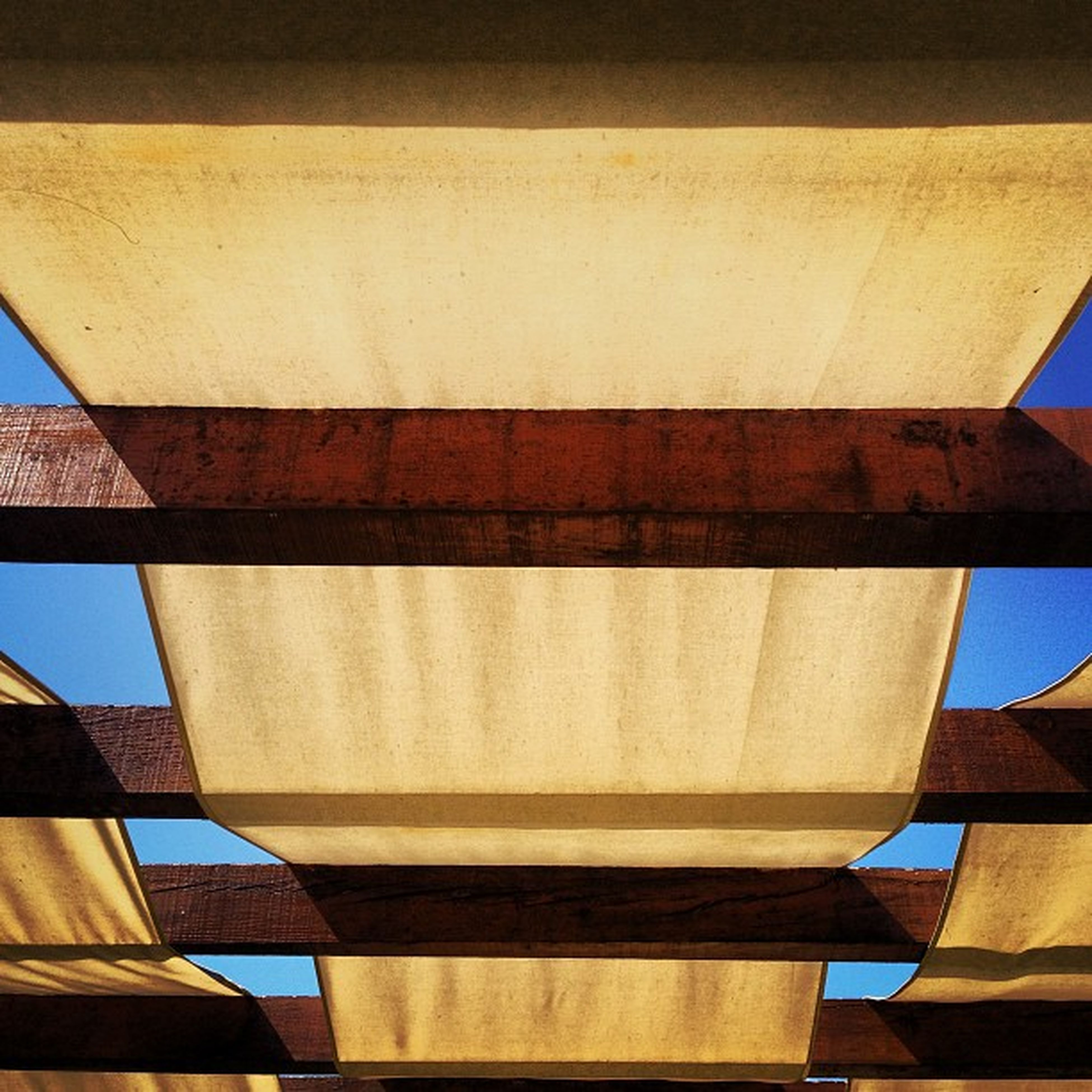 architecture, built structure, low angle view, building exterior, modern, no people, building, indoors, day, sunlight, railing, blue, sky, pattern, part of, city, directly below, window, architectural feature