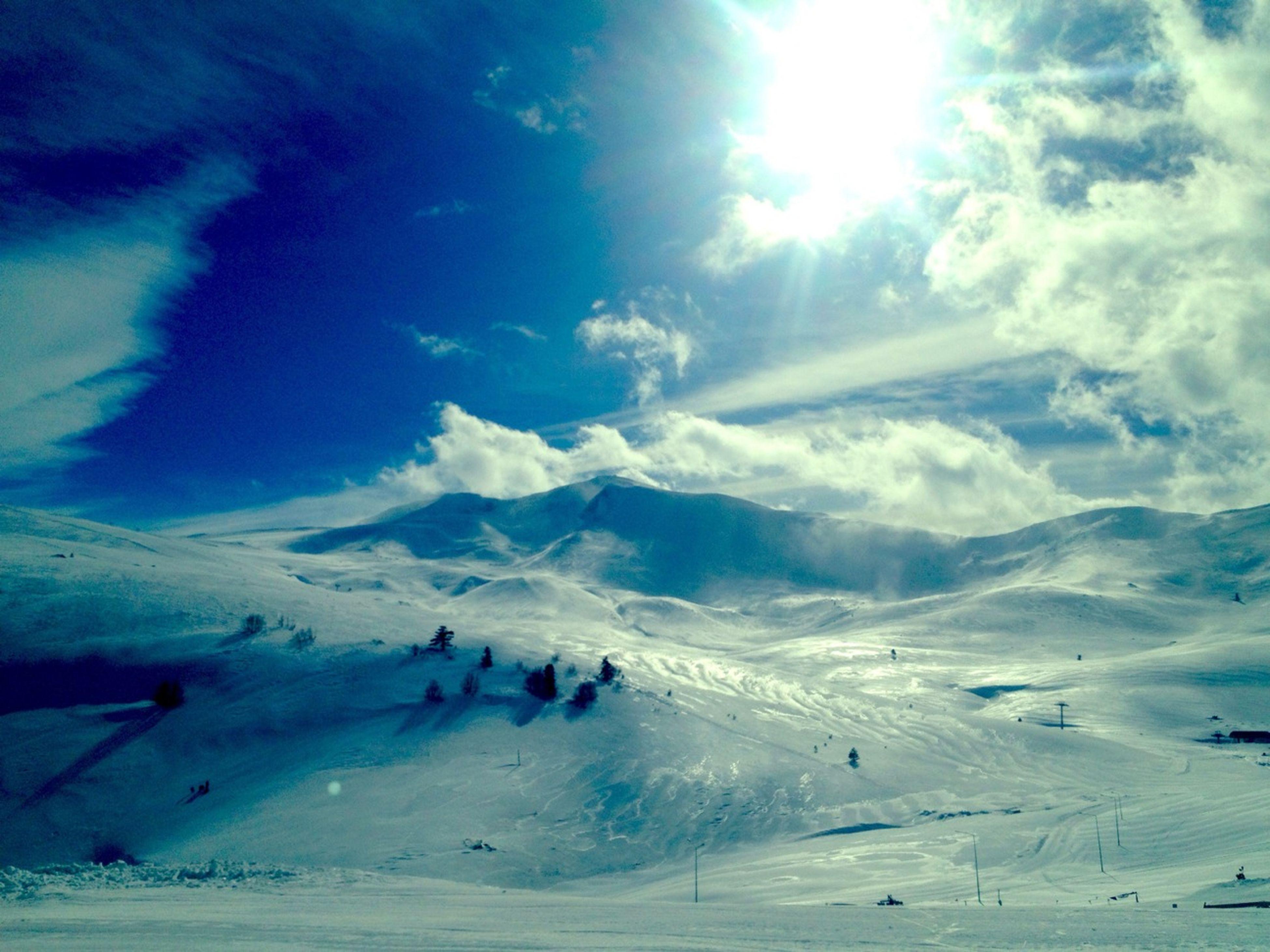 sky, snow, beauty in nature, tranquility, tranquil scene, winter, scenics, cold temperature, blue, nature, cloud - sky, landscape, sunlight, weather, mountain, cloud, day, sunbeam, sun, idyllic