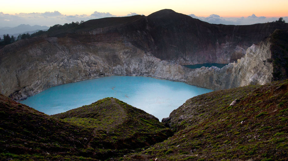 High panoramic view of the green turquoise colored lake in the Kelimutu volcano during the morning at sunrise with nobody around, Indonesia. ASIA Beauty In Nature Blue Lake Colored Water Crater Lake Flores High Angle View High Viewpoint INDONESIA Kelimutu Kelimutu Lake Kelimutu National Park Mountain Mountaintop View Nature No People Outdoors Scenics Tranquil Scene Tranquility Travel Destinations Turquoise Lake Volcanic Crater Volcanic Landscape Volcano Crater