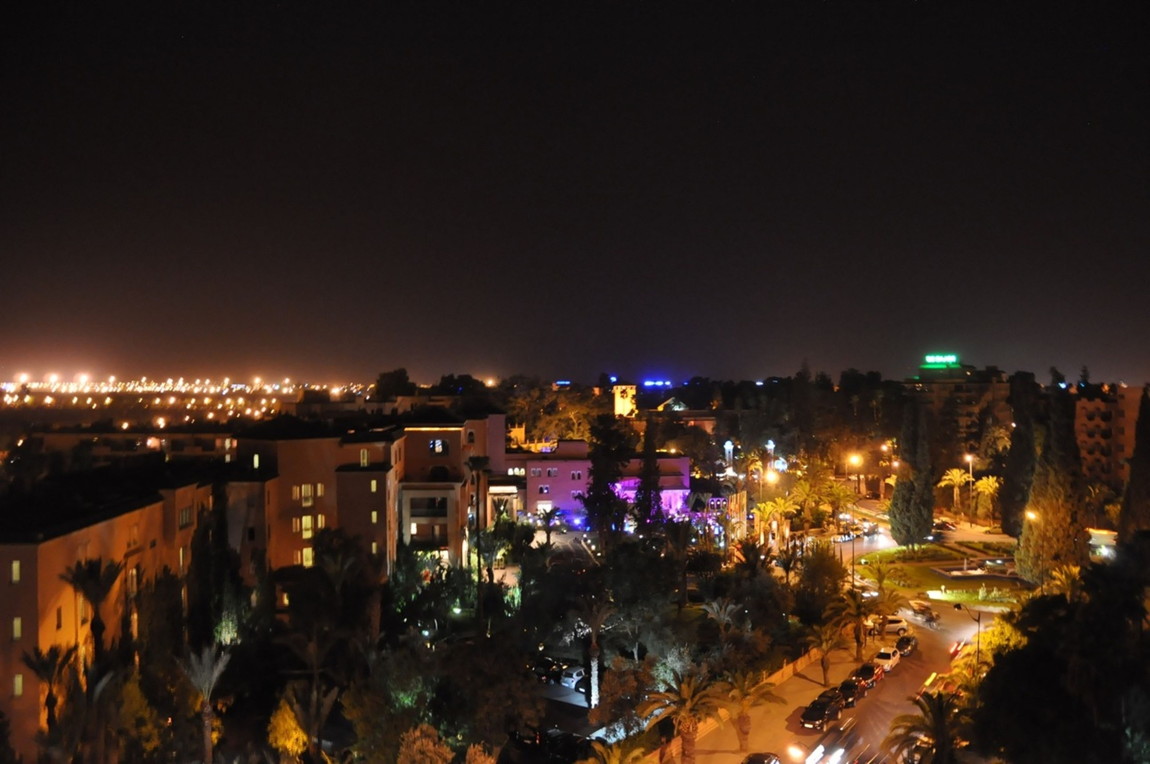 illuminated, building exterior, night, city, architecture, cityscape, built structure, high angle view, residential district, crowded, residential building, residential structure, clear sky, copy space, city life, skyscraper, sky, outdoors, office building, no people