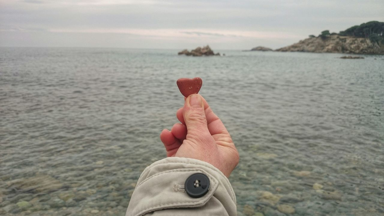 Cropped Image Man Holding Heart Shape Pebble In Front Of Sea