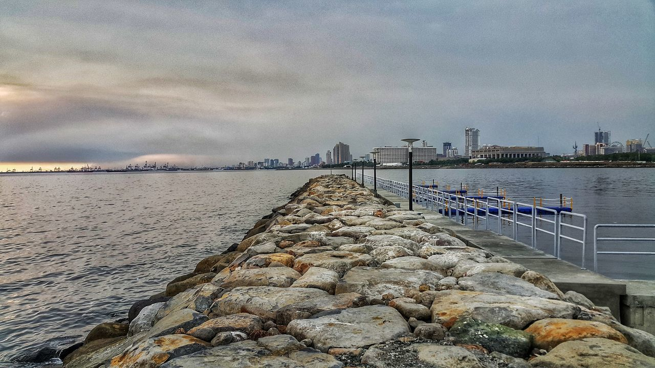 water, built structure, sky, architecture, building exterior, sea, cloud - sky, outdoors, no people, nature, city, skyscraper, day, beauty in nature, groyne, harbor