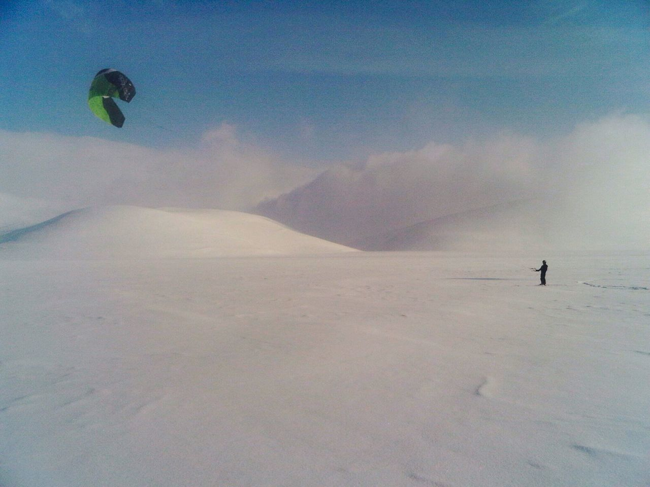 Adventure Winter Leisure Activity Cold Temperature Snow Unrecognizable Person Extreme Sports White Snowcapped Mountain Extreme Weather Wind Power Wind Real People Lifestyles Parachute Nature One Person Outdoors Day Landscape Sky Scenics Paragliding Cloud - Sky Beauty In Nature