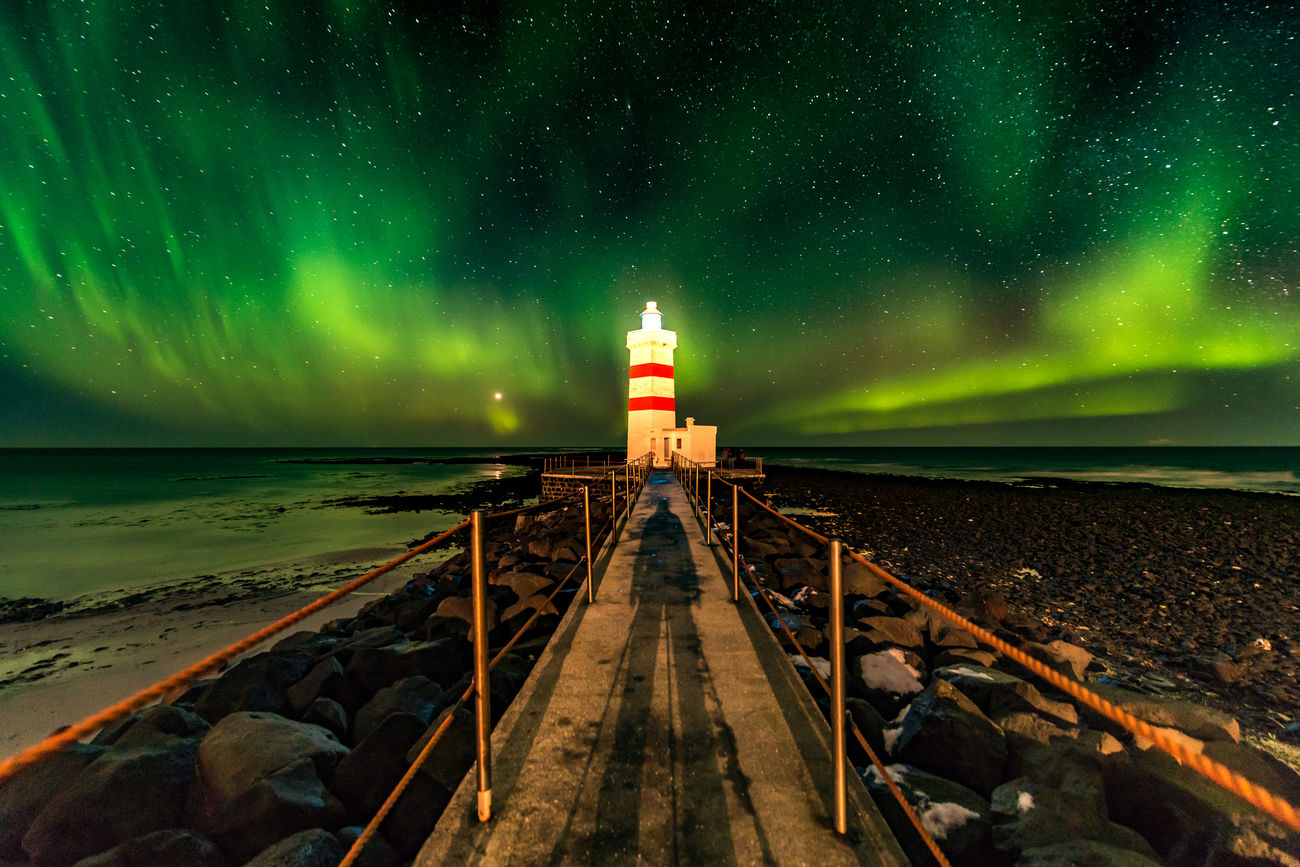 """""""So, where are the lights?"""" In the south west of Iceland, you can find the Gardur lighthouse. With a bit of luck you will be able to experience the aurora here, as I did on the first night of my latest Icelandic journey. This location can be hard to photograph after the coaches with Chinese and American tourist arrive. One friendly American lady came up to me and asked me: """"The guide took us here on an aurora tour. So where are the lights? Do you know where we should go to see it?"""" """"Erm... yes, I do."""" Astronomy Aurora Aurora Polaris Beach Copy Space Gardur Garður Horizon Over Water Iceland Illuminated Journey Landscape Lighthouse Long Exposure Nature Night No People Northern Lights Outdoors Scandinavia Scenics Sea Space Space And Astronomy Travel"""