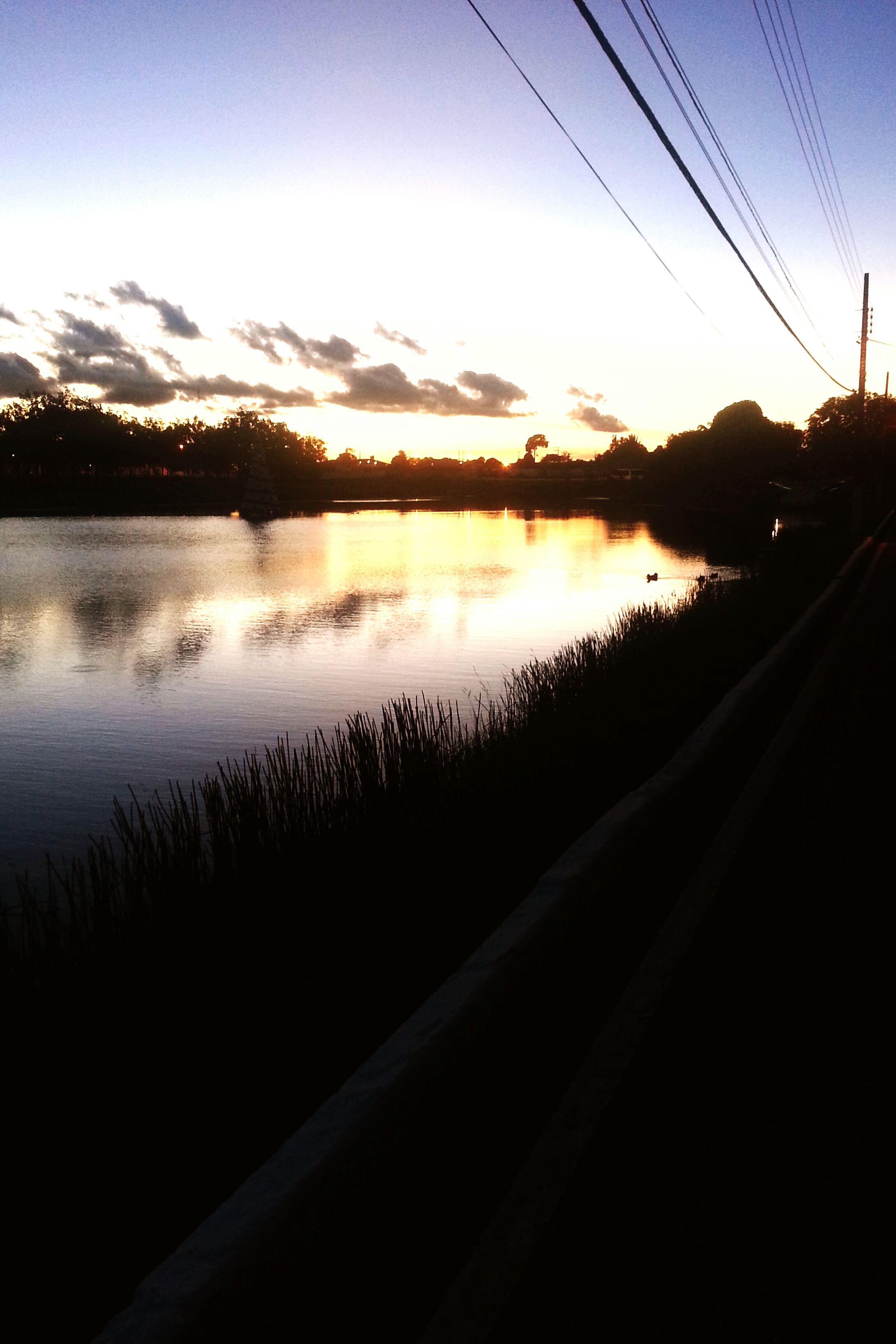 sunset, water, reflection, silhouette, lake, sky, tranquil scene, scenics, tranquility, sun, beauty in nature, river, nature, tree, sunlight, orange color, transportation, electricity pylon, idyllic, power line