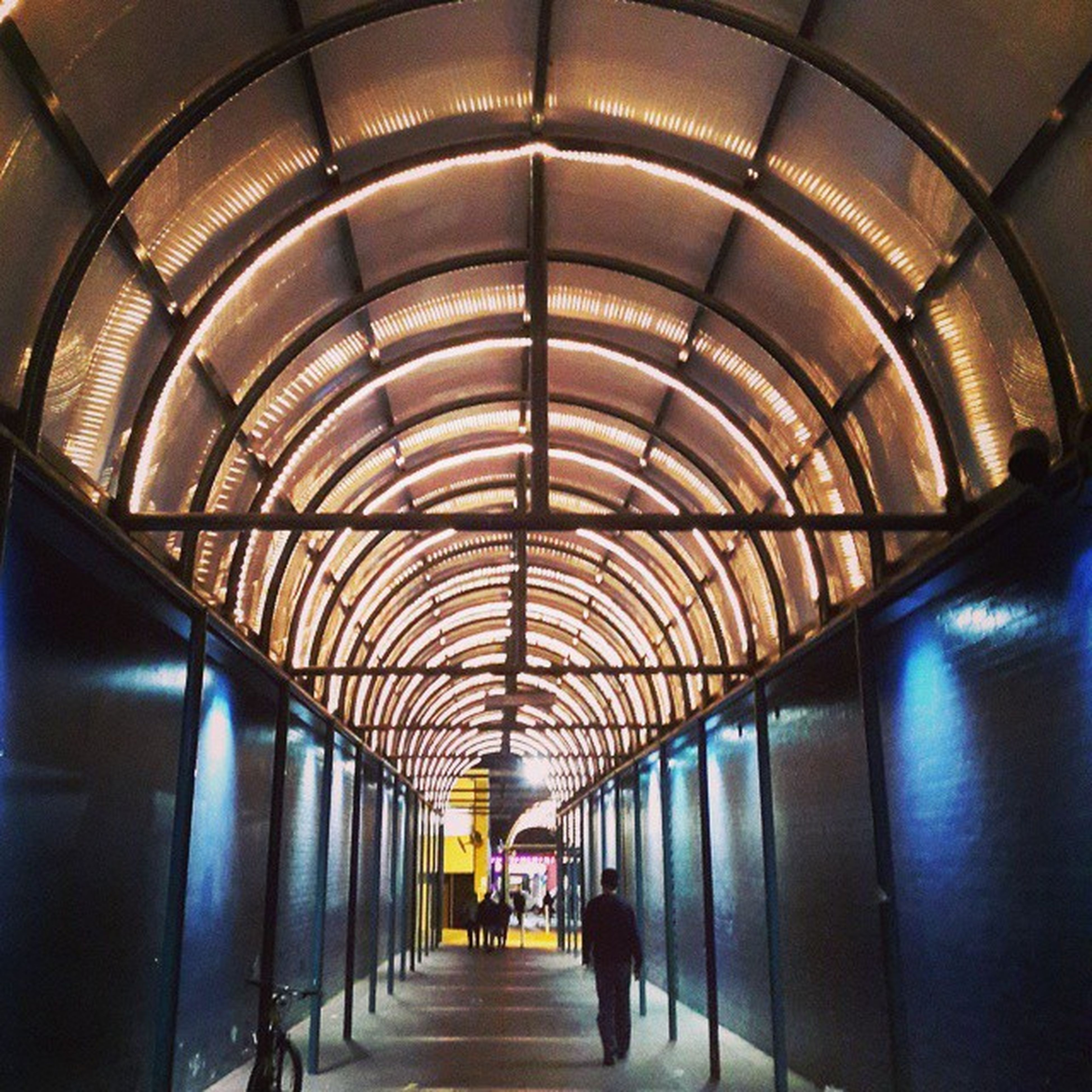 indoors, ceiling, the way forward, illuminated, diminishing perspective, corridor, lighting equipment, arch, in a row, architecture, built structure, tunnel, vanishing point, subway, walking, empty, incidental people, flooring, transportation