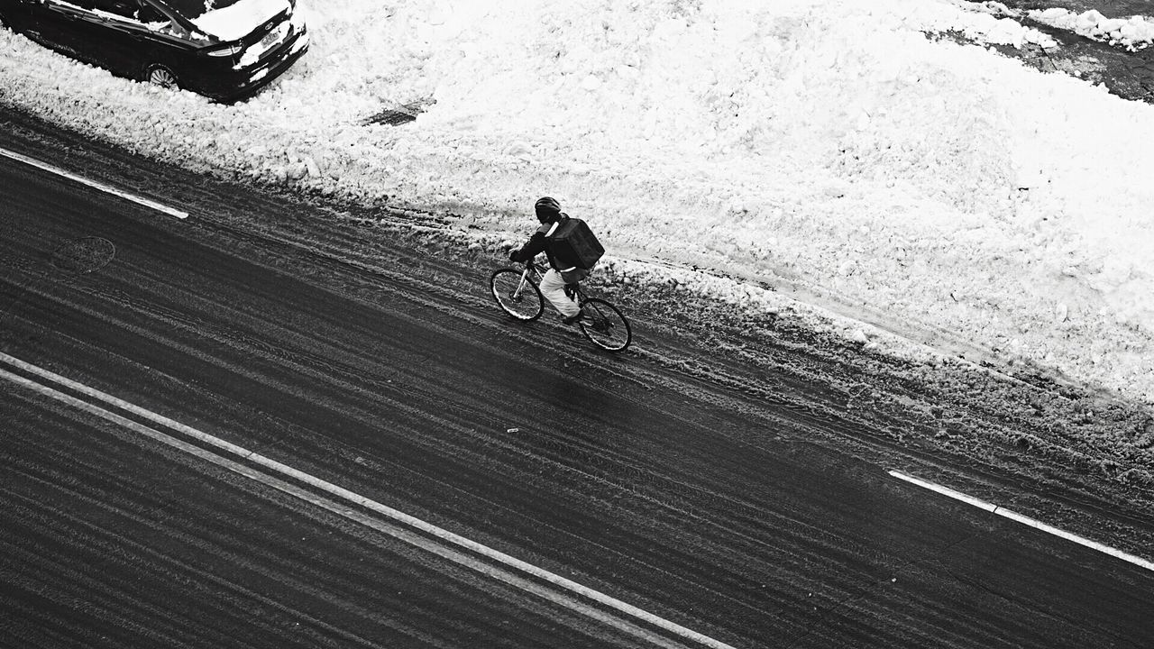 High Angle View Of Person Riding Bicycle On Street By Snow