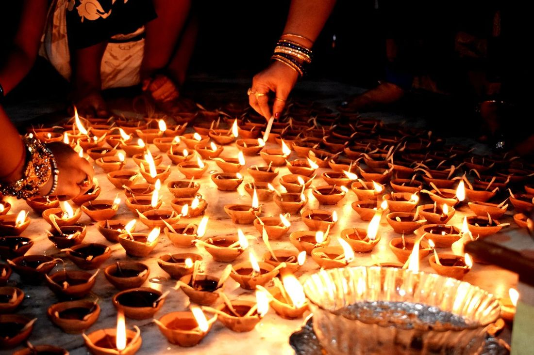 A Festival of Lights : Diwali Flame Burning Heat - Temperature Candle Celebration Diwali People Adult Human Body Part Sweet Food Arrangement Food And Drink Food Large Group Of Objects Temptation Diya - Oil Lamp Bangle Illuminated Human Hand Night Festival First Eyeem Photo