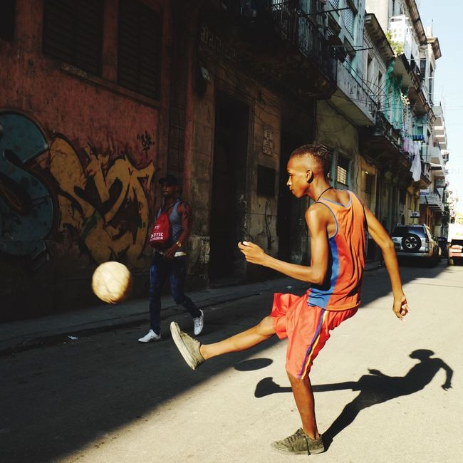 Architecture Built Structure Full Length Building Exterior Street Lifestyles City Casual Clothing Young Adult Outdoors Footpath Person Outside Ball Street Football Football Boy Kicking