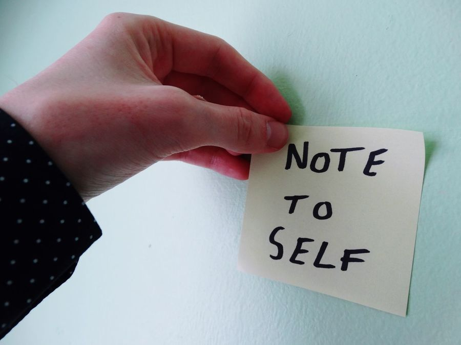 Person putting note on wall. Text Western Script Human Hand Communication Human Body Part Indoors  One Person Human Finger Close-up Message Real People Day Voting People Note Notes Hand Person Sticky Note Note To Self