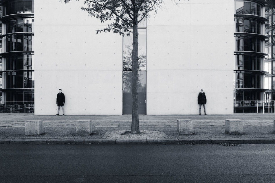Two people standing in symmetry against concrete walls Architecture Architecture Blackandwhite Building Exterior Built Structure City Concrete Couple Day Human Left And Right Men Outdoors People Real People Scale  Size Sky Symmetry Tree Two Walking Wall Welcome To Black