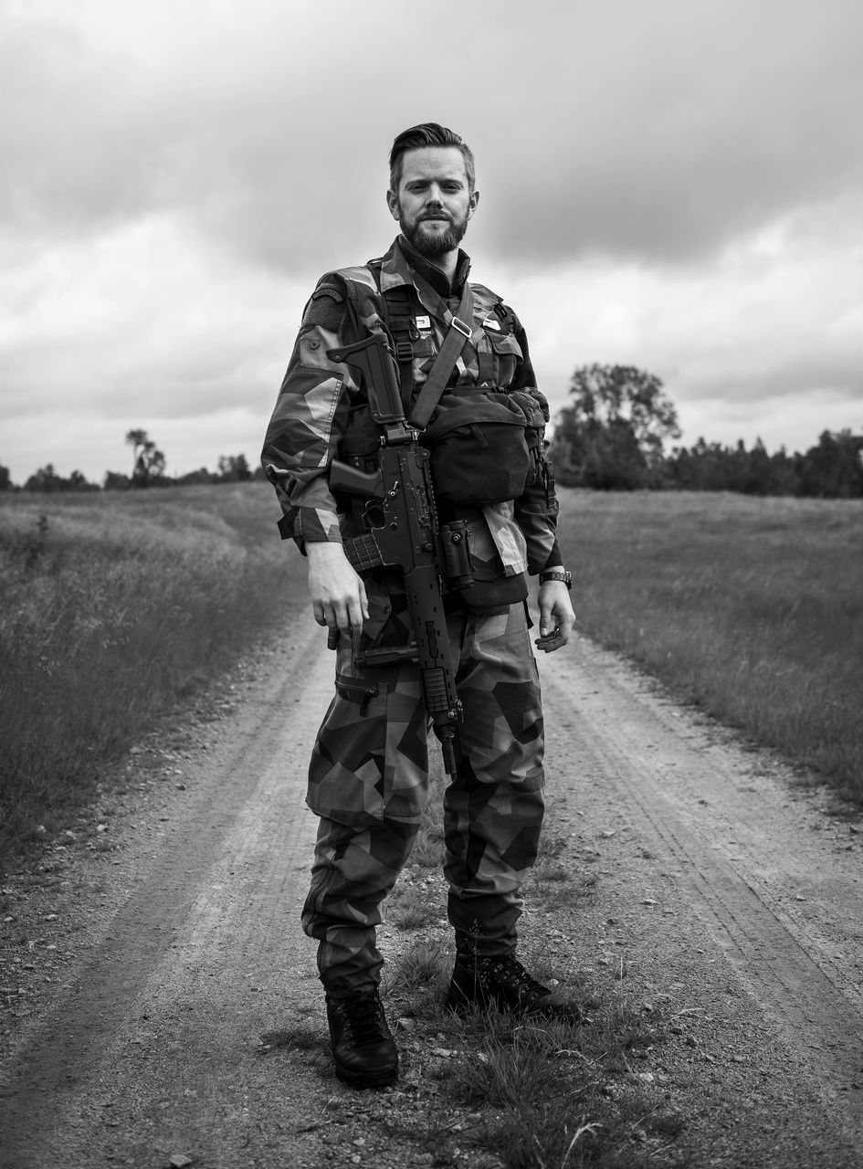field, one person, full length, sky, cloud - sky, real people, standing, grass, outdoors, front view, day, landscape, army, helmet, men, military, looking at camera, military uniform, portrait, young adult, one man only, army soldier, camouflage clothing, only men, adults only, adult, people