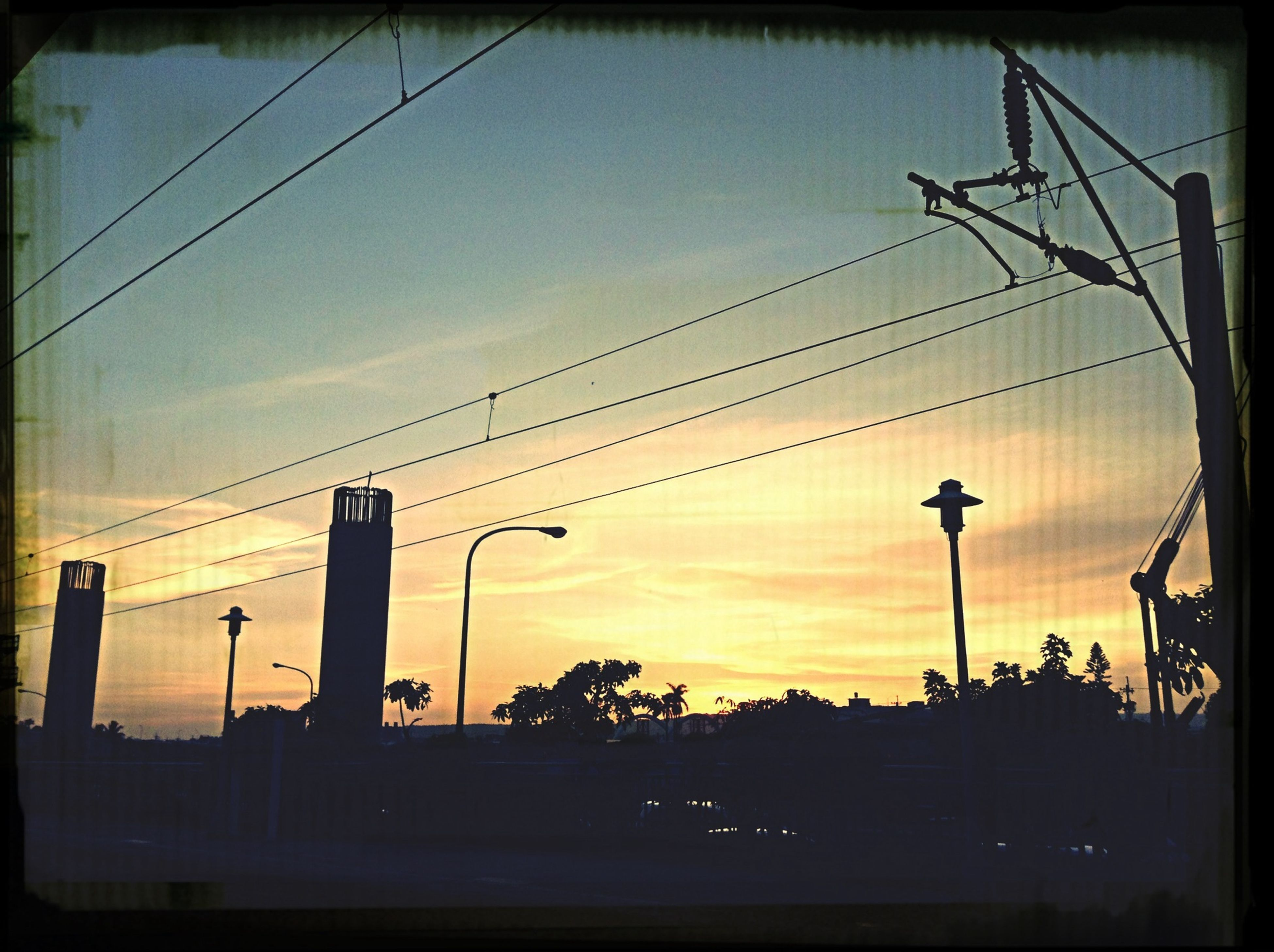 power line, electricity pylon, sunset, power supply, electricity, cable, silhouette, transfer print, sky, connection, fuel and power generation, power cable, building exterior, low angle view, built structure, technology, architecture, auto post production filter, street light, dusk