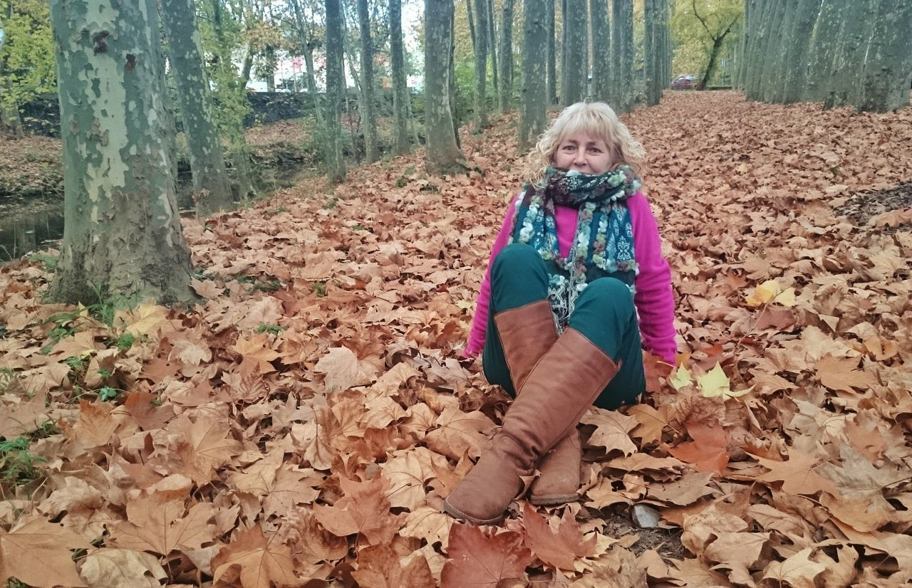 Portrait Of Mature Woman Relaxing Leaves Covered Street In Park During Autumn