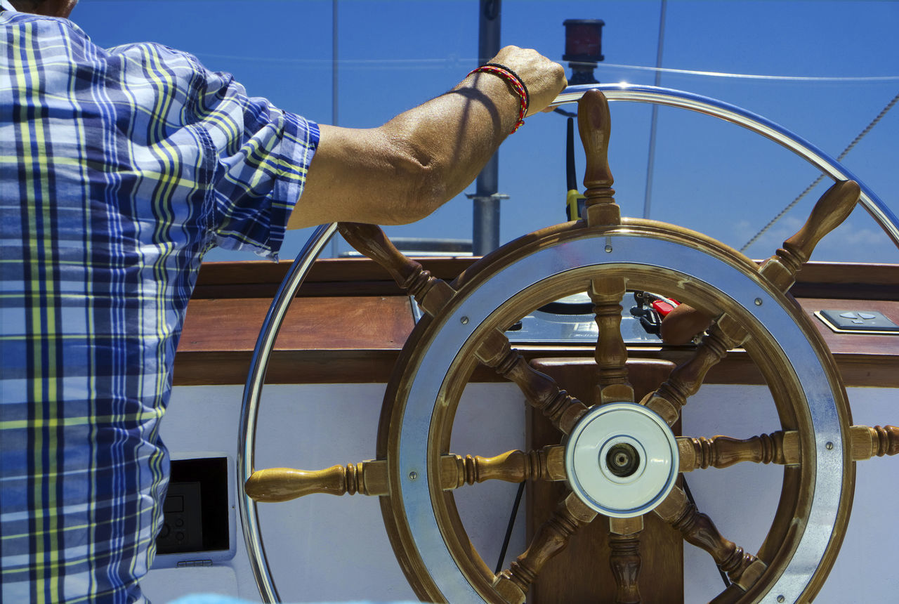 Captain at wooden steering wheel of a sailing boat Backside View Captain Chequered Shirt Clear Blue Sky Control Controls Freedom Helm Helmet Nautical Nautical Vessel Navigation Only Men Outside Recreation  Relaxing Rudder Sailing Ship Sailor Ship Steersman Summer Wooden Post Yacht Boat