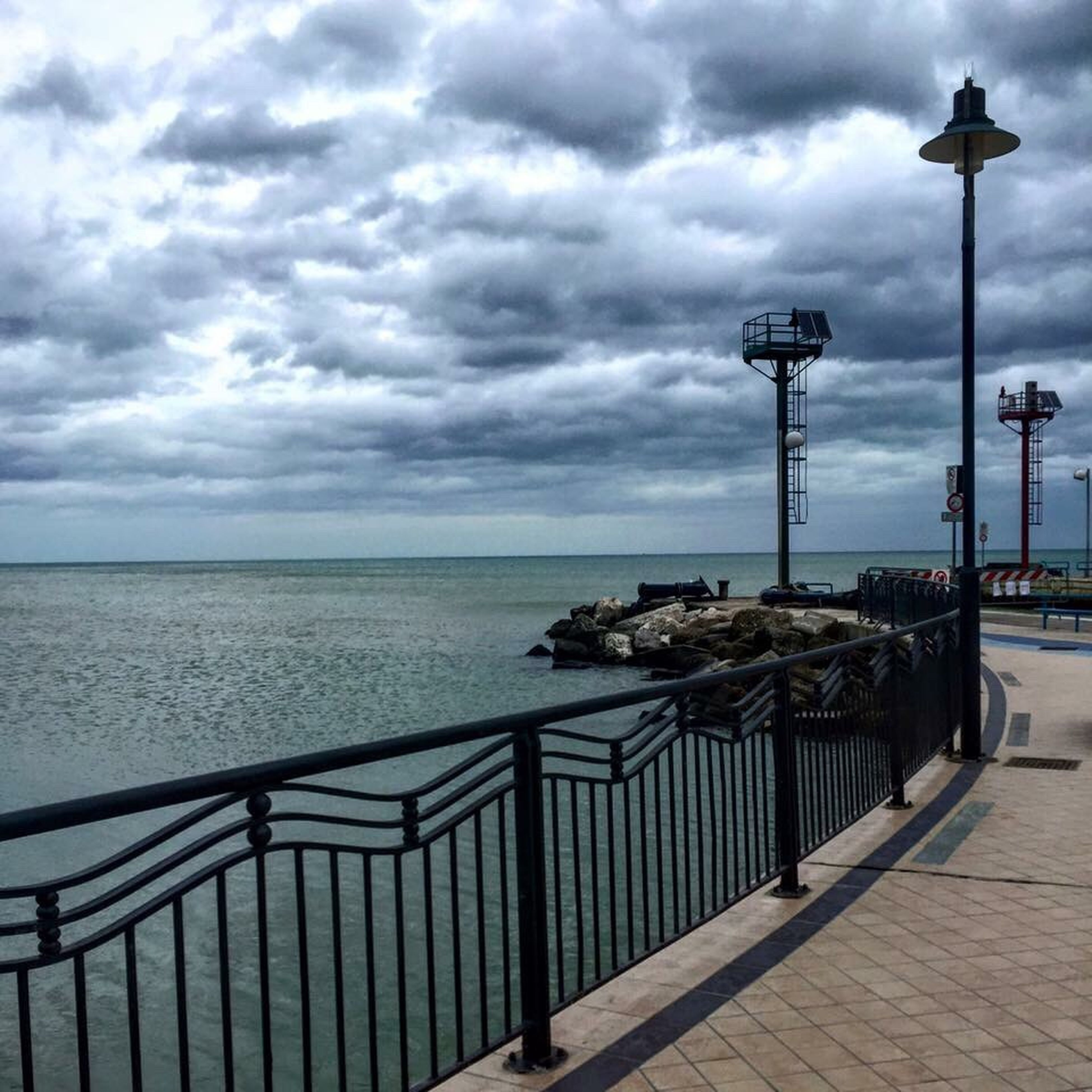 sea, horizon over water, sky, water, cloud - sky, cloudy, railing, street light, scenics, tranquility, tranquil scene, beach, pier, cloud, beauty in nature, nature, weather, shore, overcast, lighting equipment