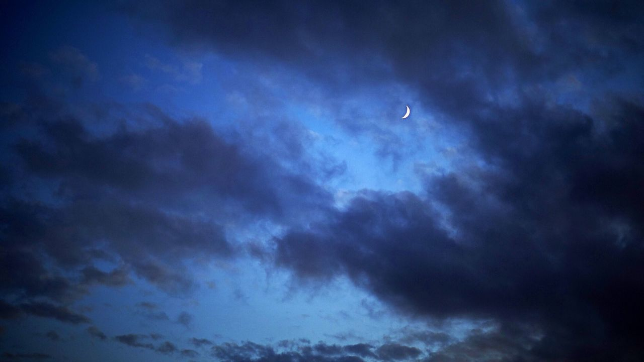 Low Angle View Of Cloudy Sky With Moon At Dusk