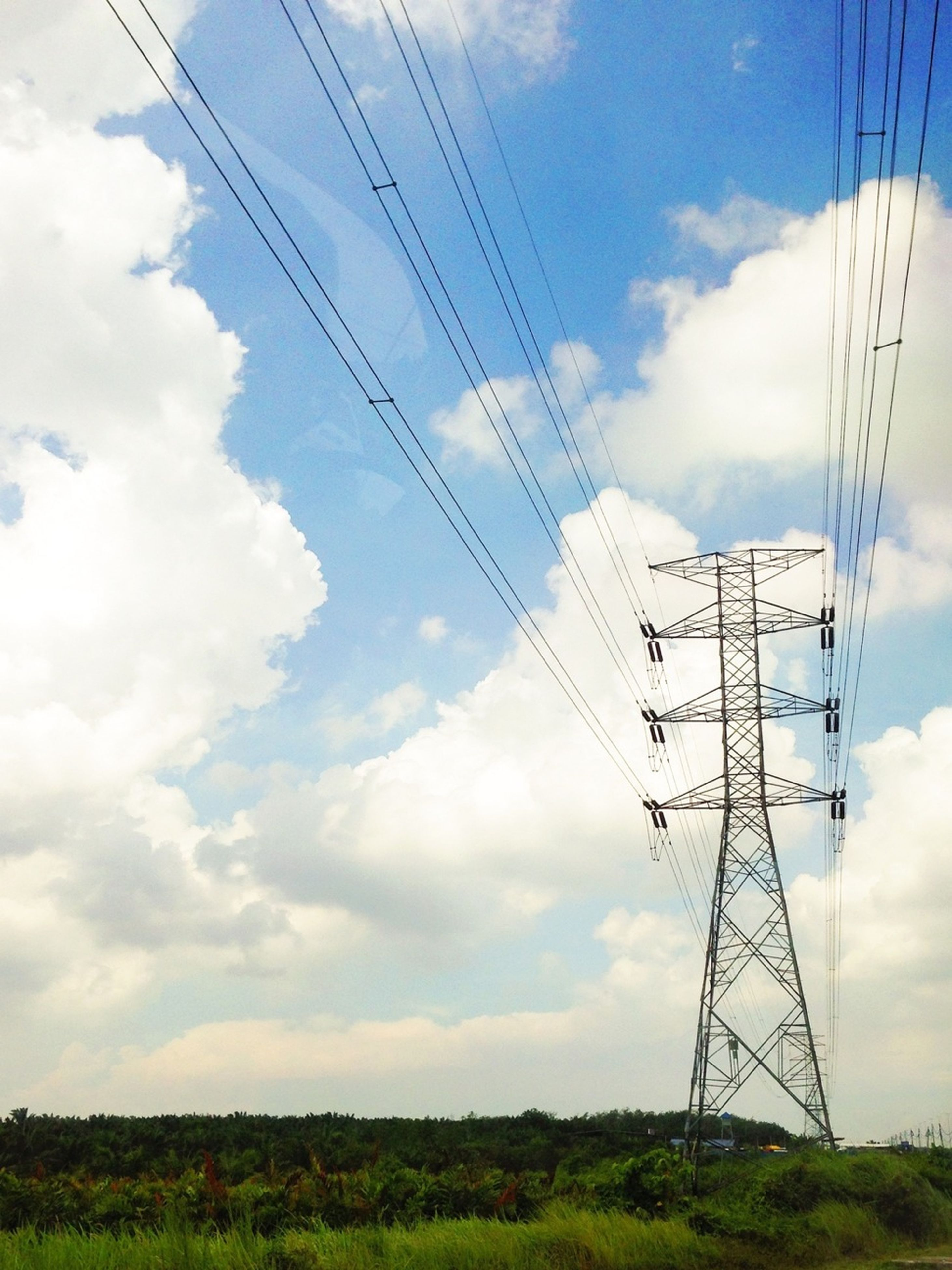 electricity pylon, power line, electricity, power supply, fuel and power generation, connection, cable, technology, sky, cloud - sky, low angle view, power cable, cloud, field, landscape, cloudy, nature, blue, electricity tower, outdoors