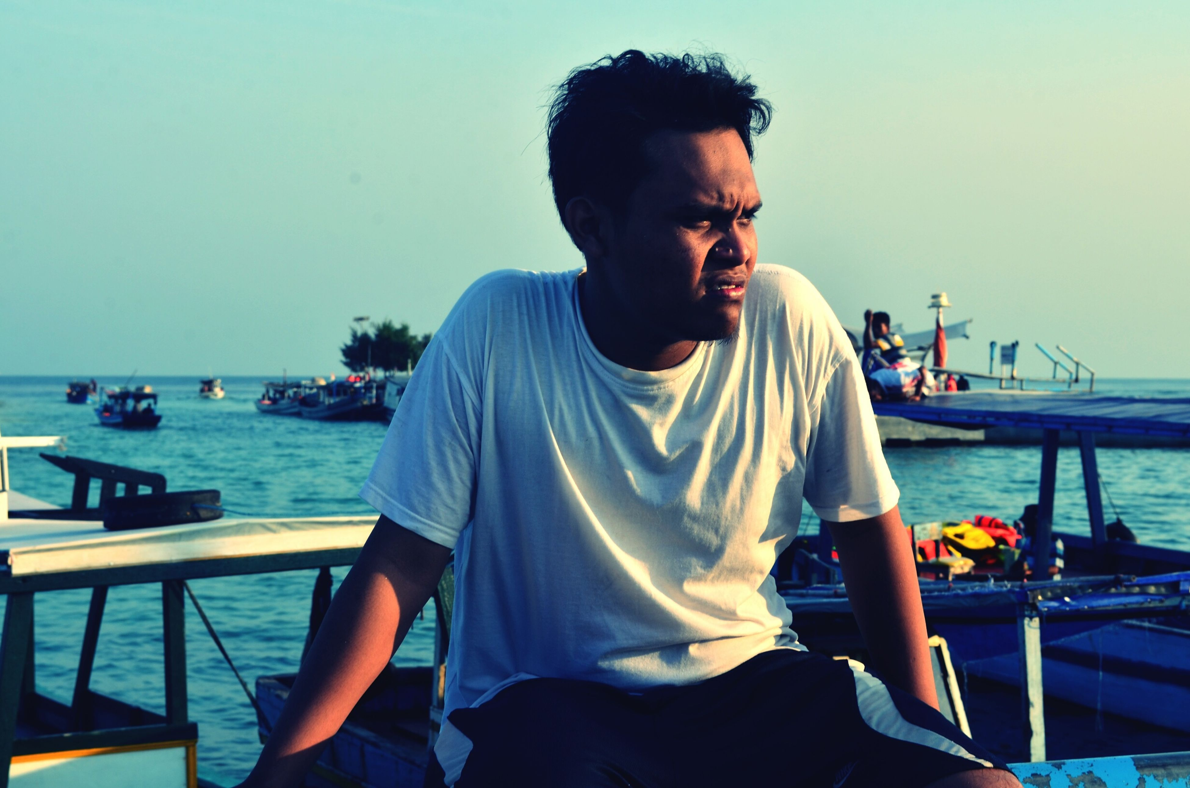 water, nautical vessel, lifestyles, sea, transportation, person, young adult, mode of transport, leisure activity, casual clothing, young men, boat, clear sky, sitting, sunglasses, travel, portrait, waist up