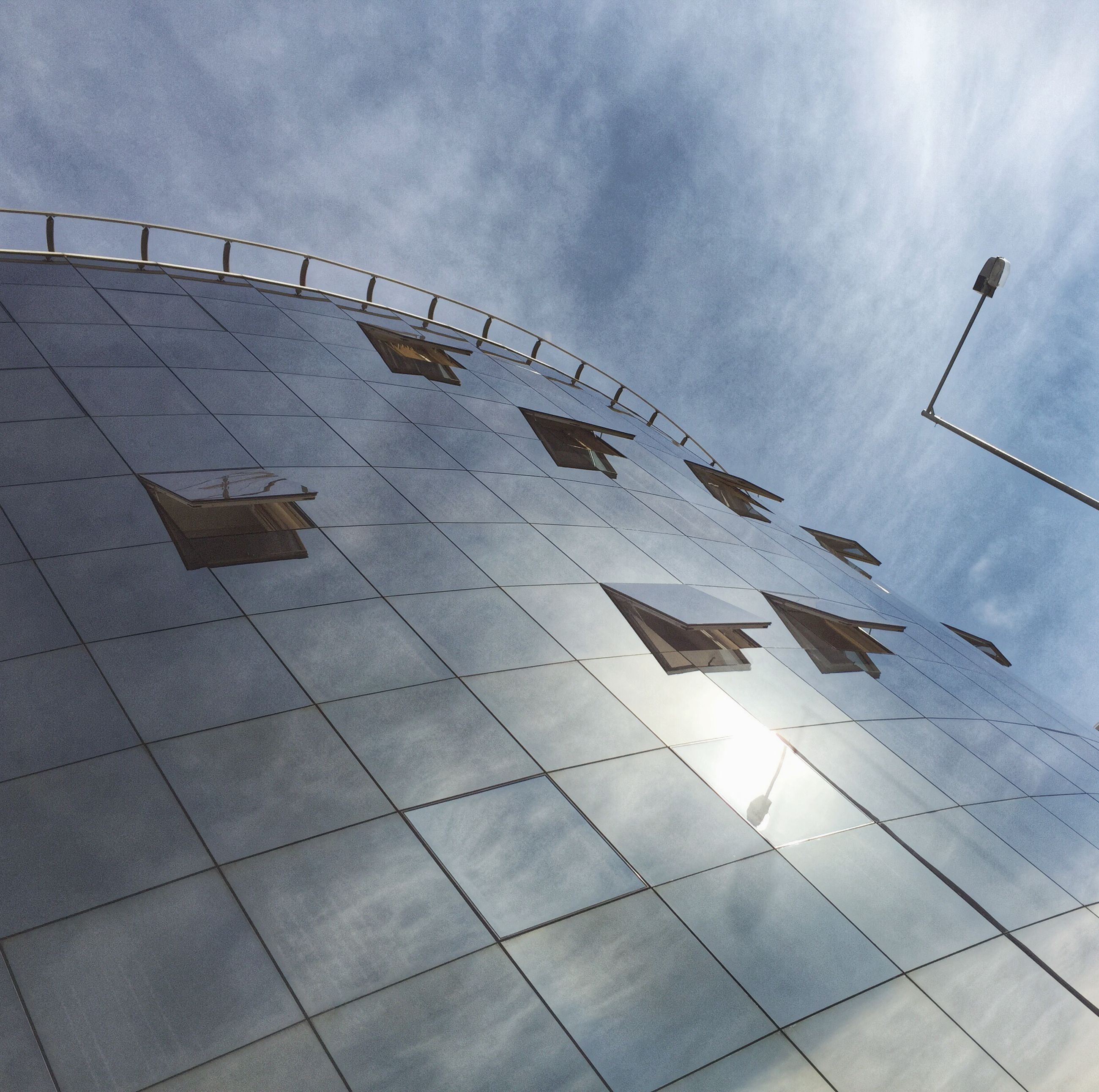 sky, low angle view, built structure, architecture, cloud - sky, flying, building exterior, day, cloudy, bird, outdoors, no people, pattern, art and craft, art, cloud, mid-air, creativity, modern, sunlight