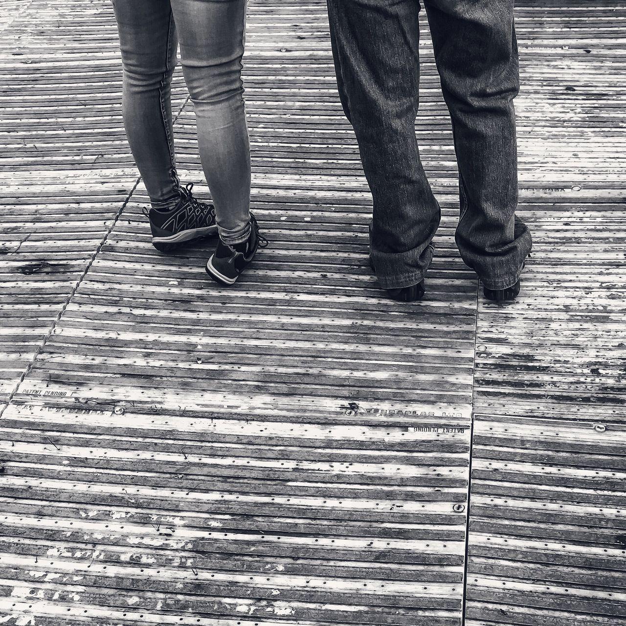 low section, person, lifestyles, shoe, men, standing, leisure activity, human foot, walking, jeans, street, cobblestone, footwear, casual clothing, sidewalk