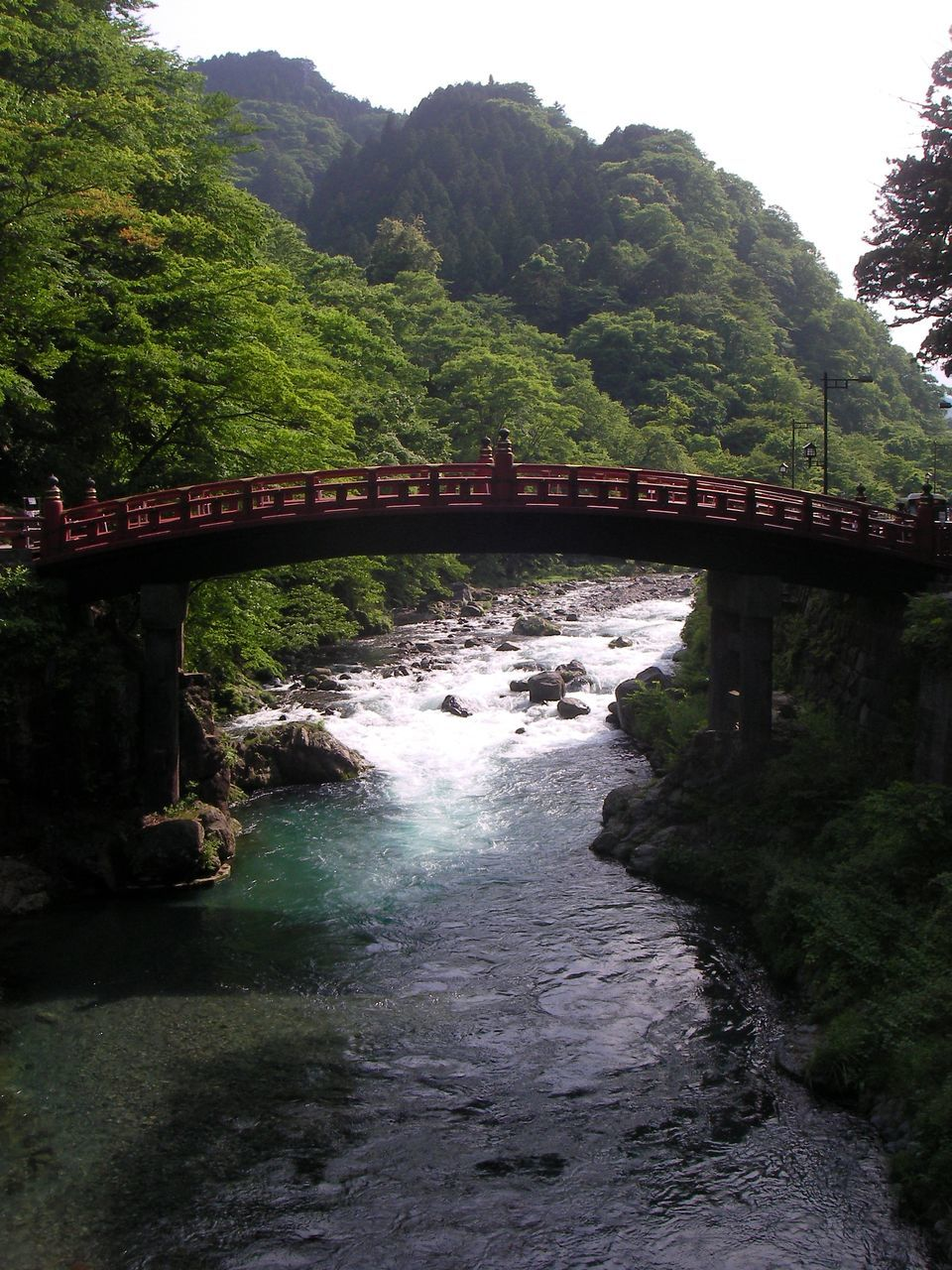 bridge - man made structure, connection, river, water, tree, day, nature, built structure, outdoors, arch, architecture, mountain, transportation, no people, forest, beauty in nature, growth, scenics, footbridge, sky