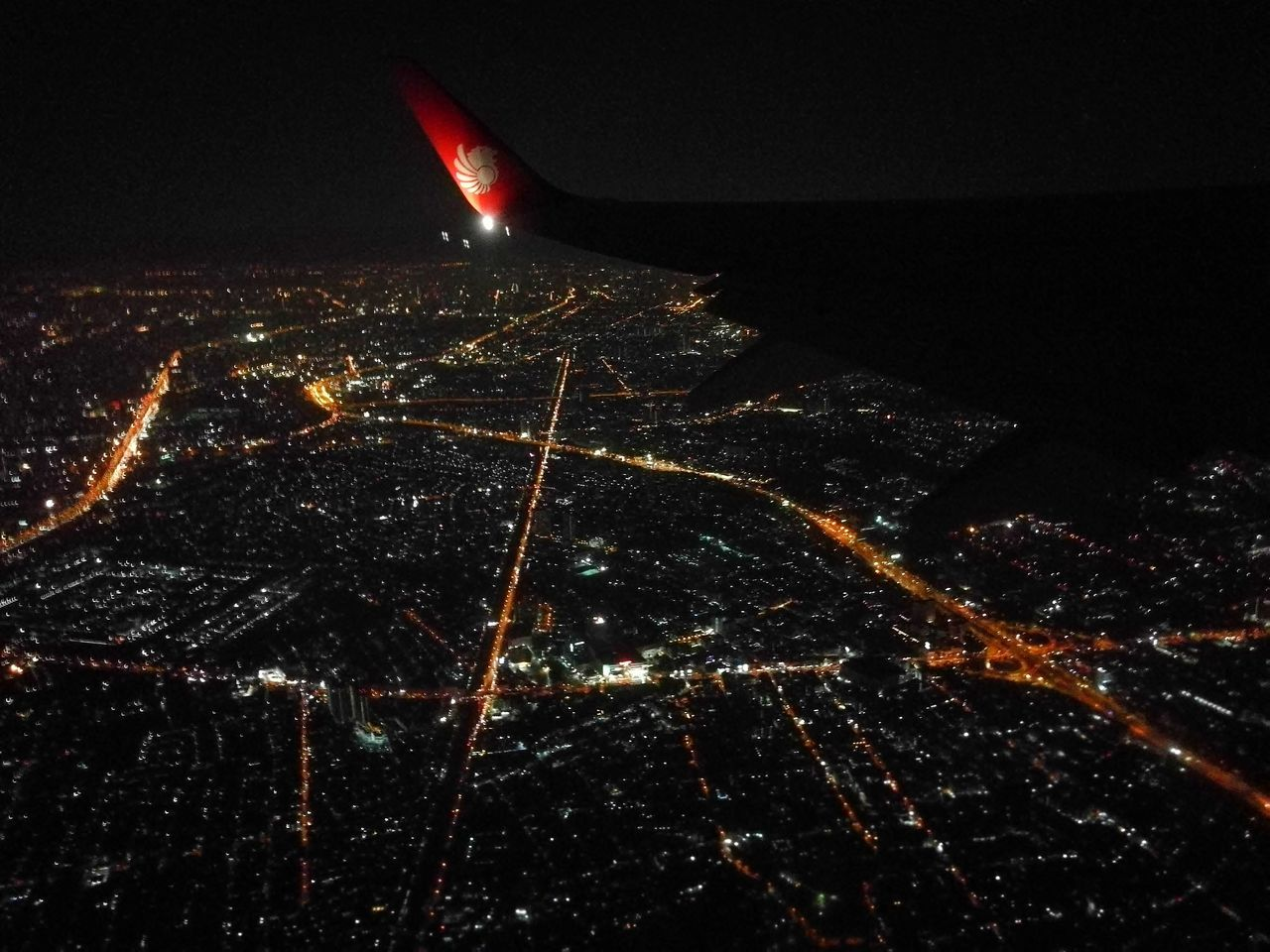 night, illuminated, cityscape, no people, aerial view, city, airplane, outdoors, air vehicle, architecture, building exterior, flying, sky, airplane wing