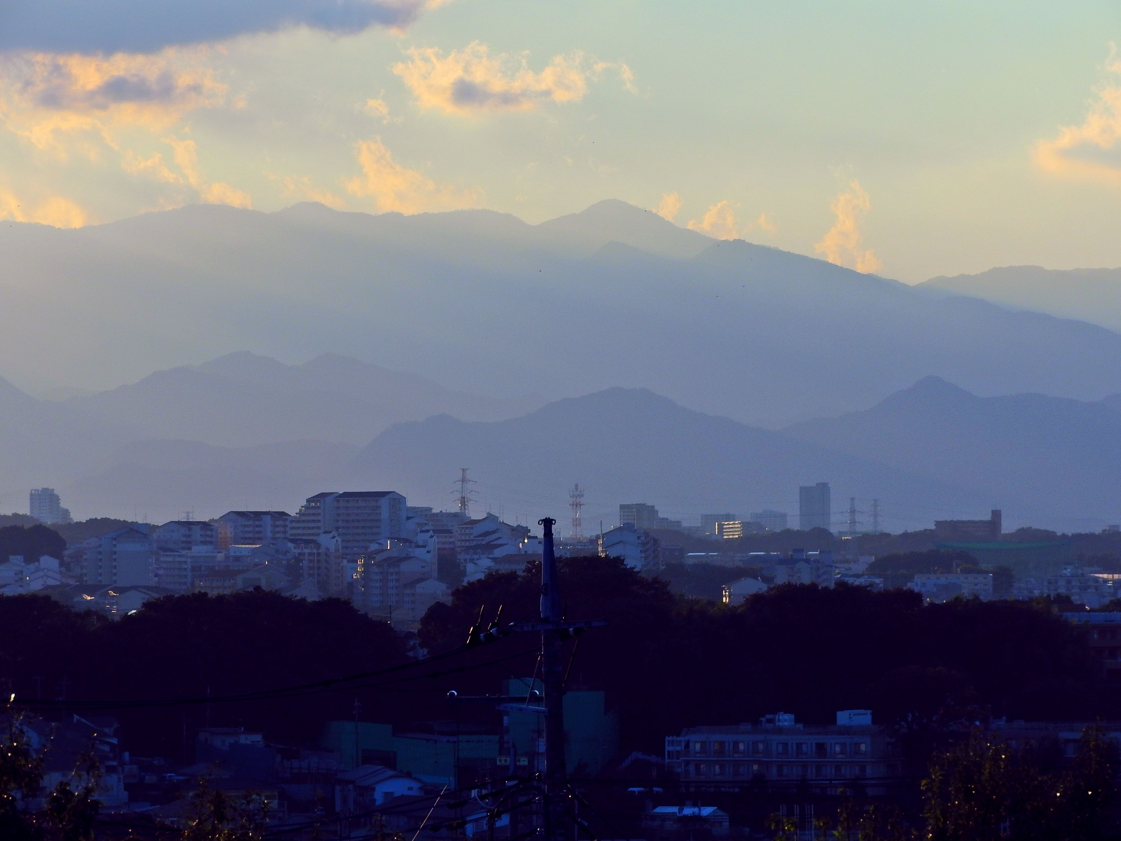 city, architecture, sunset, mountain, building exterior, cityscape, built structure, silhouette, no people, dusk, sky, nature, outdoors, mountain range, skyscraper, beauty in nature, day