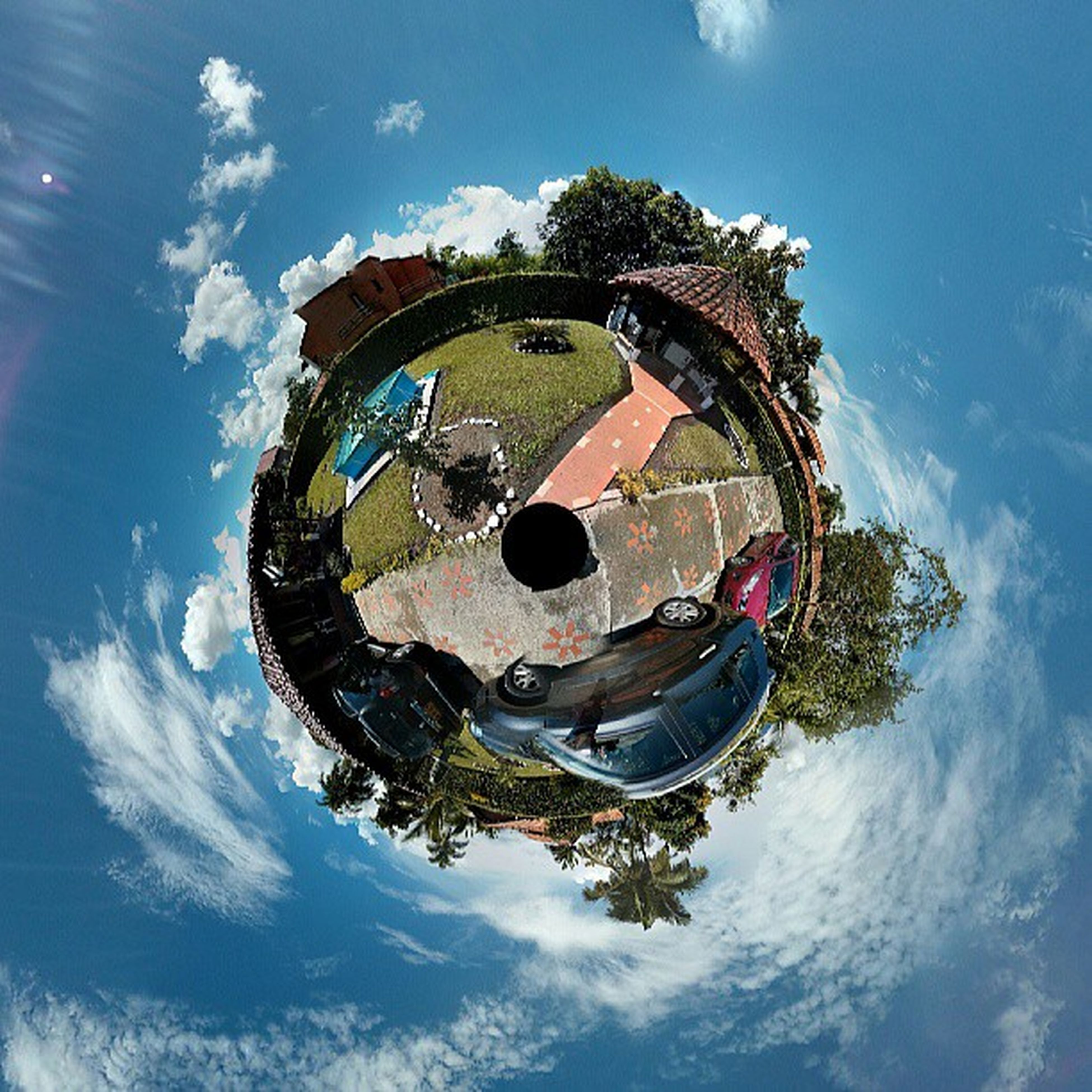 sky, cloud - sky, circle, ferris wheel, cloud, built structure, low angle view, blue, day, water, fish-eye lens, outdoors, reflection, architecture, sunlight, nature, amusement park, amusement park ride, arts culture and entertainment, no people
