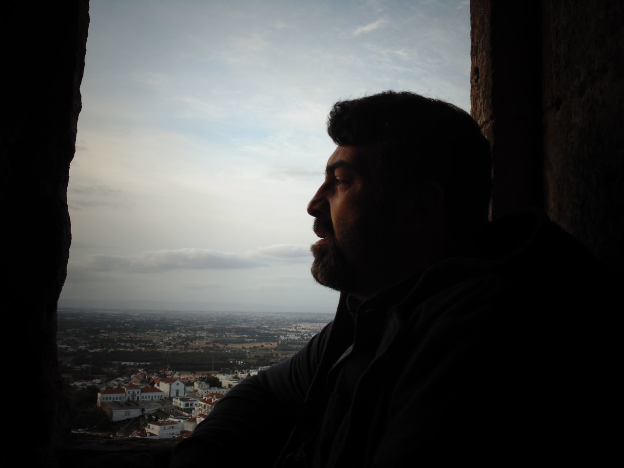 Side View Of Man Looking Away By Window Against Sky