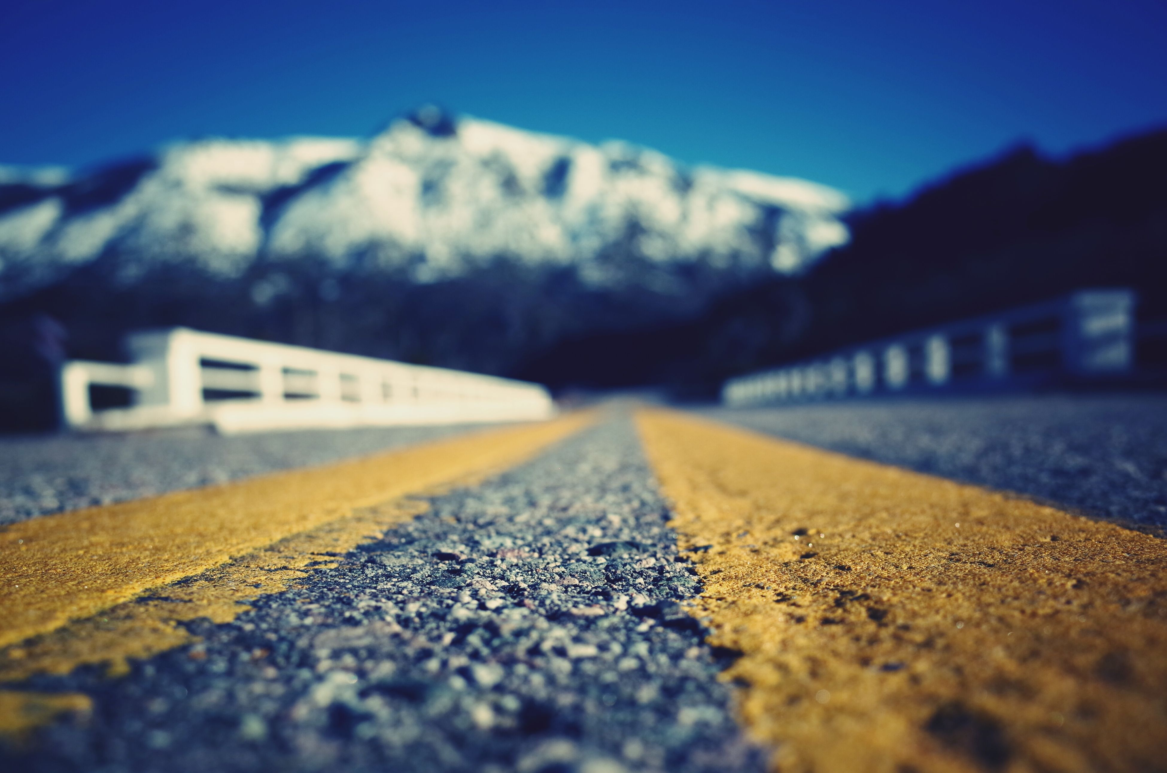surface level, selective focus, clear sky, the way forward, asphalt, road, sky, diminishing perspective, street, built structure, focus on foreground, outdoors, snow, day, transportation, railroad track, no people, winter, blue, mountain
