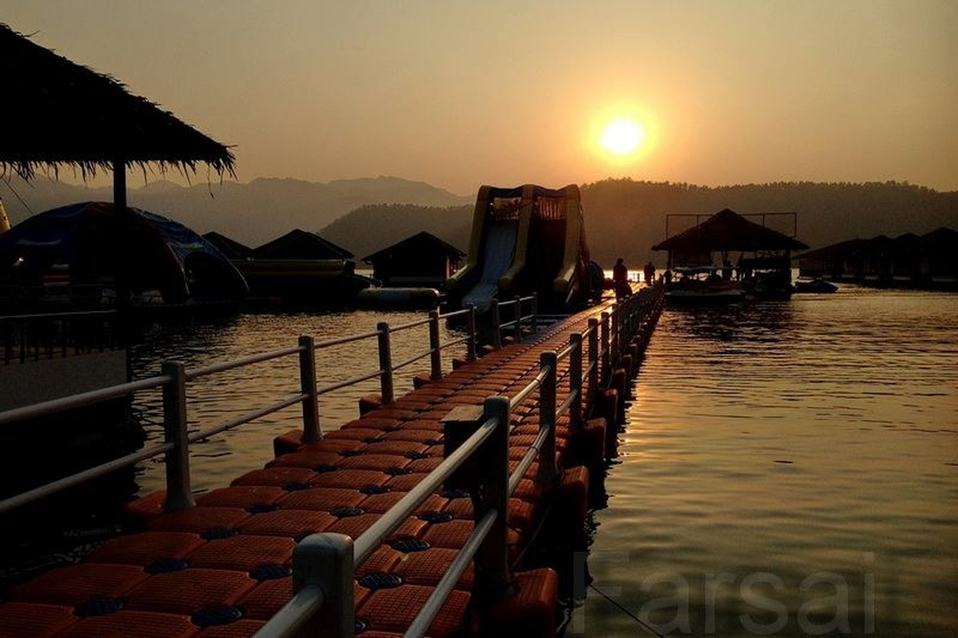 sunset, water, mountain, pier, scenics, tranquility, silhouette, tranquil scene, clear sky, mountain range, beauty in nature, sun, lake, sea, railing, nature, orange color, sky, built structure, transportation