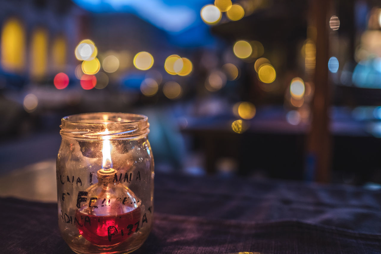 Bokeh Candle City City Life City Lights Close-up Copy Space Focus On Foreground Illuminated Night No People Oil Lamp Outdoors Restaurant Sidewalk Sidewalk Cafe Street Table Western Script