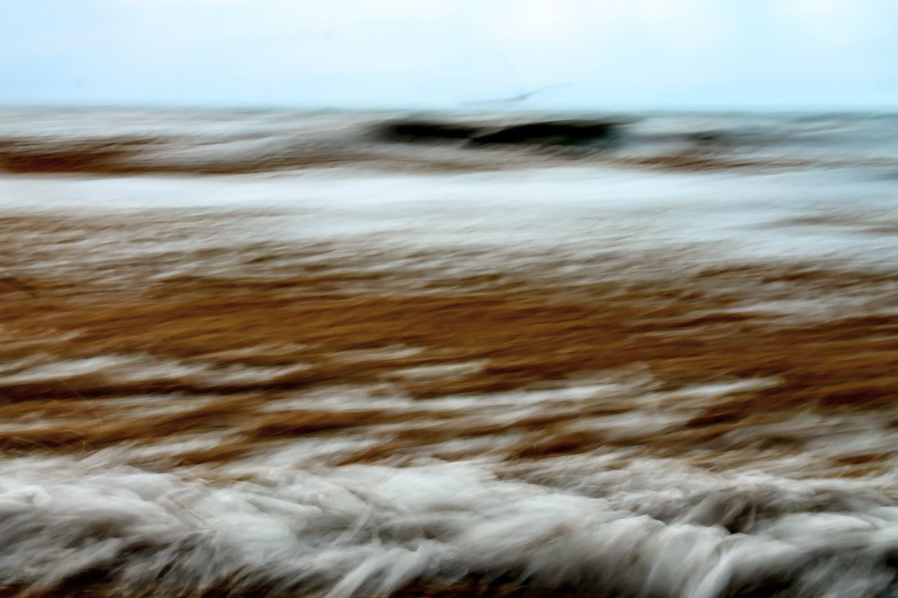 blurred motion, motion, no people, close-up, nature, beach, day, winter, sand, outdoors, backgrounds, sky, sea, beauty in nature, defocused, cold temperature, sand dune, water