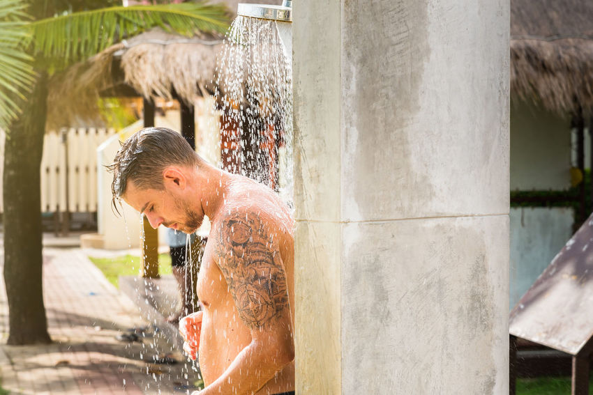 Trat, Thailand - May, 20, 2017 : Unidentified name man showering outside near swimming pool after swimming in the sea at Klong Prao Resort in Prao Beach Koh Chang island Trat, Thailand. Adult Adults Only Day Editorial  Illustrative Illustrative Editorial Leisure Activity Lifestyles Men Motion One Man Only One Person Only Men Outdoors People Real People Shirtless Splashing Spraying Thailand Water