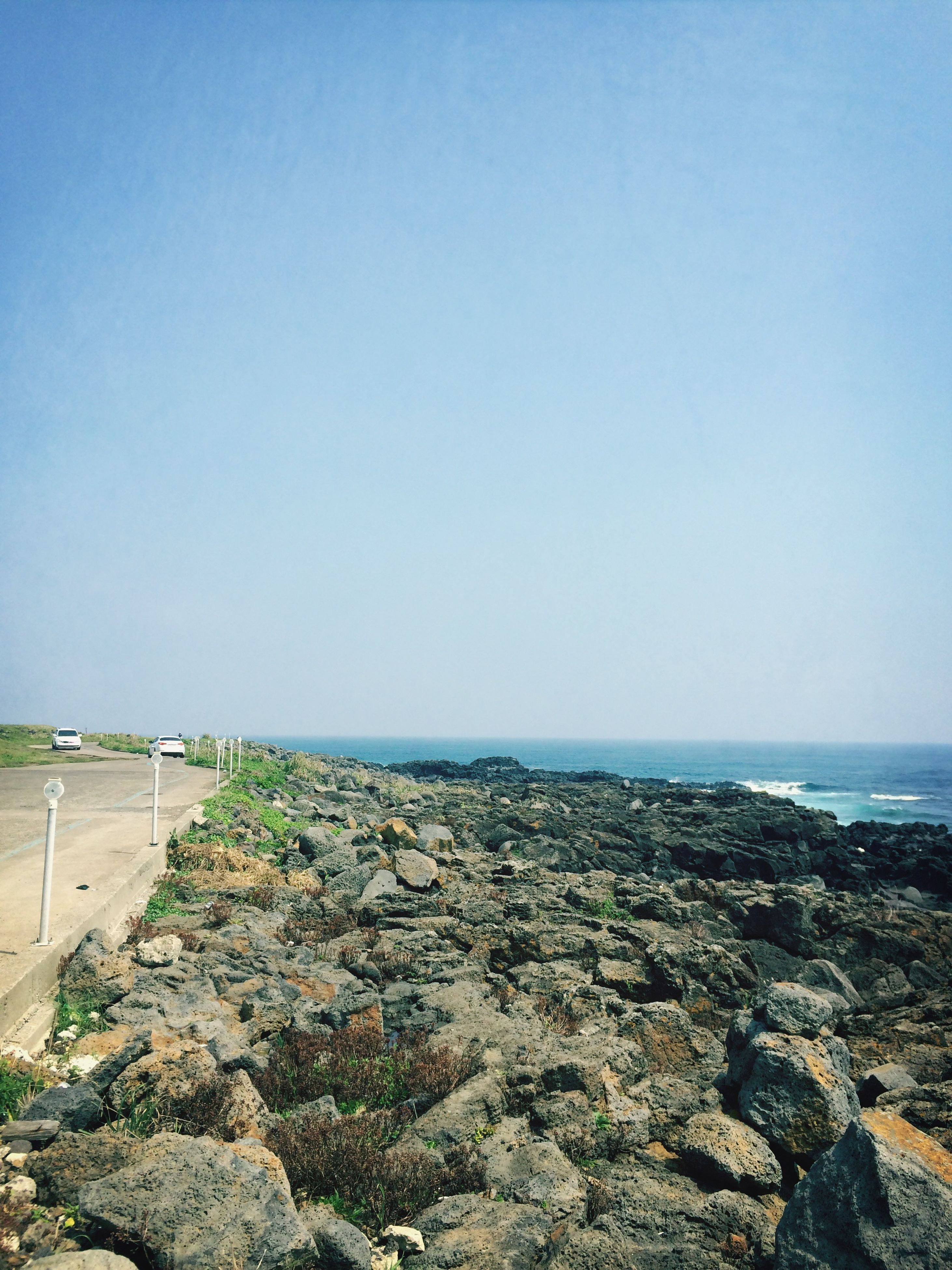 sea, clear sky, horizon over water, copy space, beach, water, tranquil scene, tranquility, shore, scenics, blue, beauty in nature, nature, sand, rock - object, coastline, idyllic, day, outdoors, non-urban scene