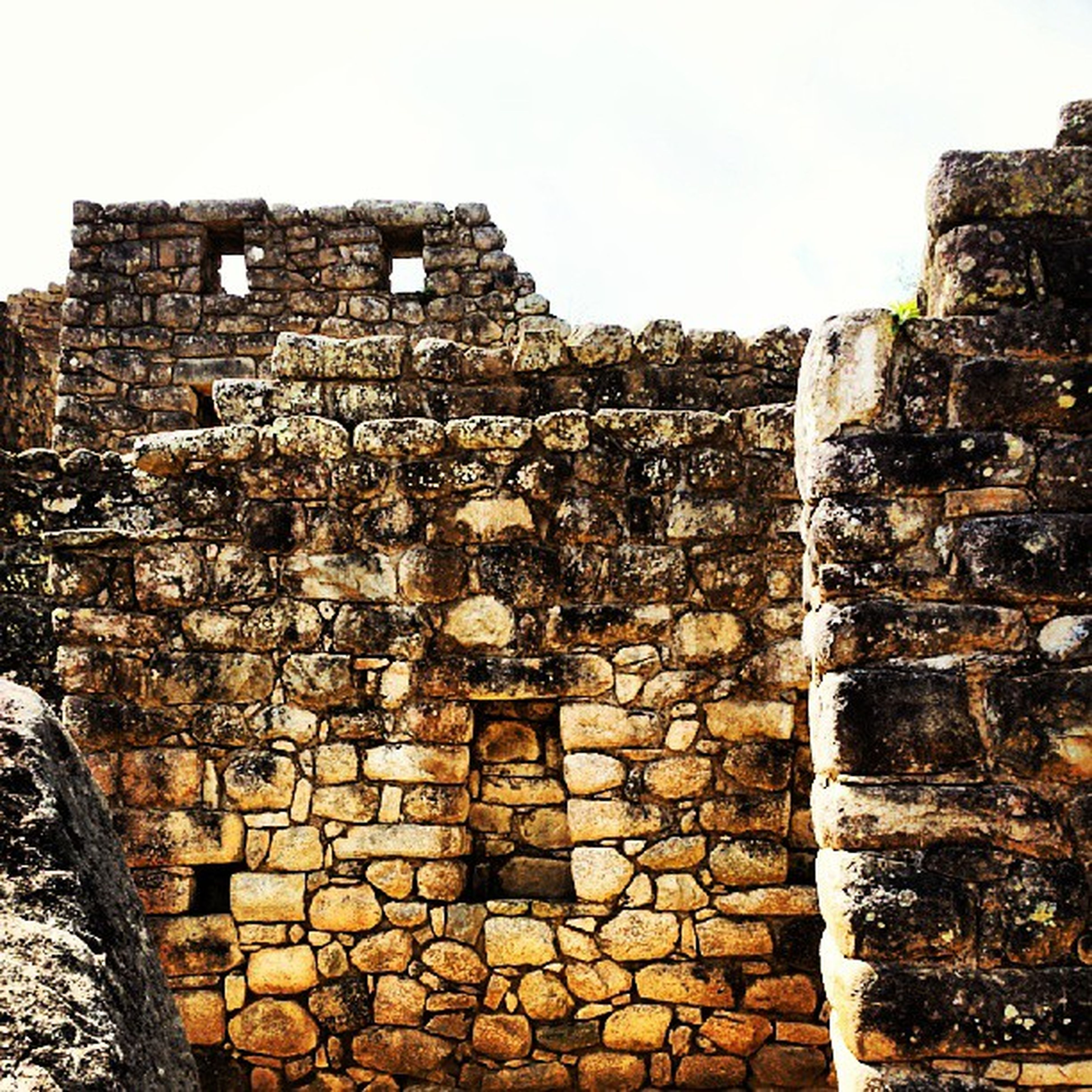 architecture, built structure, stone wall, building exterior, brick wall, old, wall - building feature, weathered, damaged, abandoned, history, old ruin, run-down, brick, obsolete, deterioration, clear sky, stone material, the past, low angle view