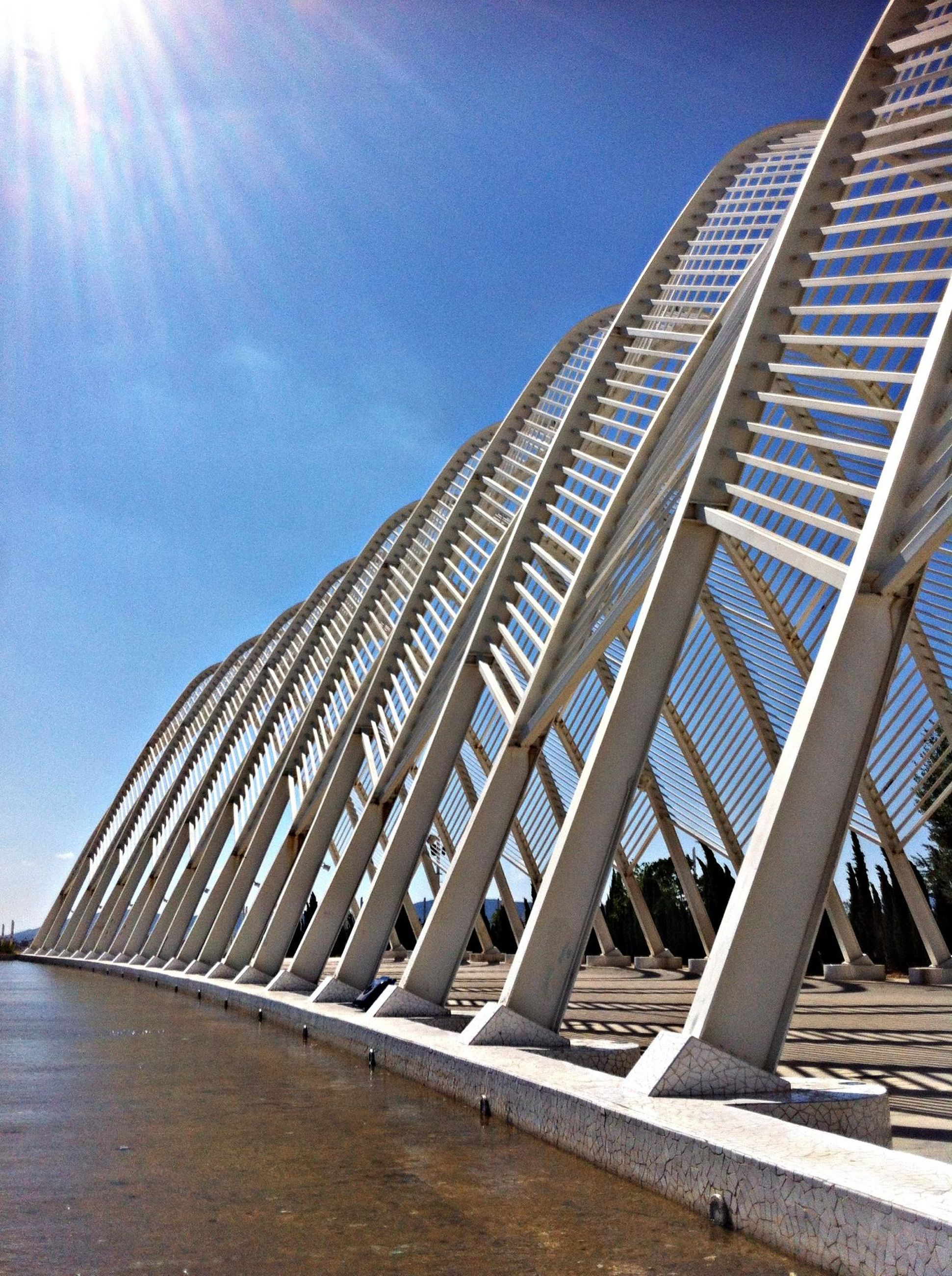 architecture, built structure, low angle view, sunlight, building exterior, sky, blue, sunbeam, sunny, modern, railing, sun, city, lens flare, tall - high, day, outdoors, clear sky, no people, bridge - man made structure