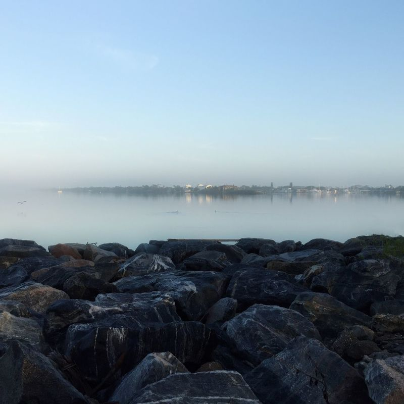 Lifting fog Melbourne Florida Indian River Lagoon Beauty In Nature Tranquility Tranquil Scene Foggy Morning Pebble Beach Rocks And Water Serene Outdoors Serene Tranquil Outdoors Serenebeauty Unruffled Calm Water Riverscape Fog Over Water Hard And Soft