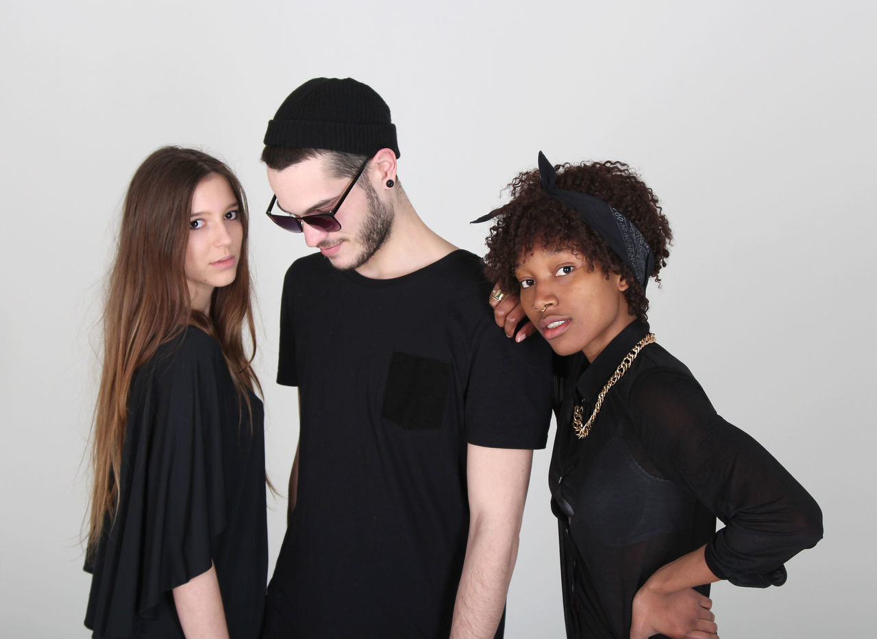 studio shot, white background, young women, young adult, black color, togetherness, friendship, young men, standing, smiling, lifestyles, fashion model